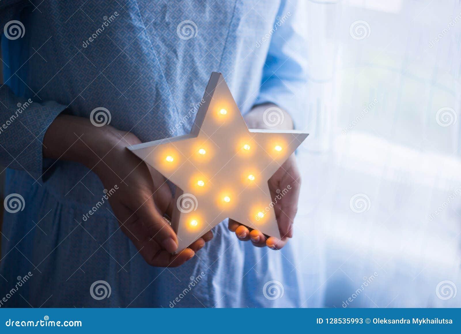 Mãos fêmeas macias do close up que guardam a estrela festiva de incandescência do diodo emissor de luz perto da janela na luz do