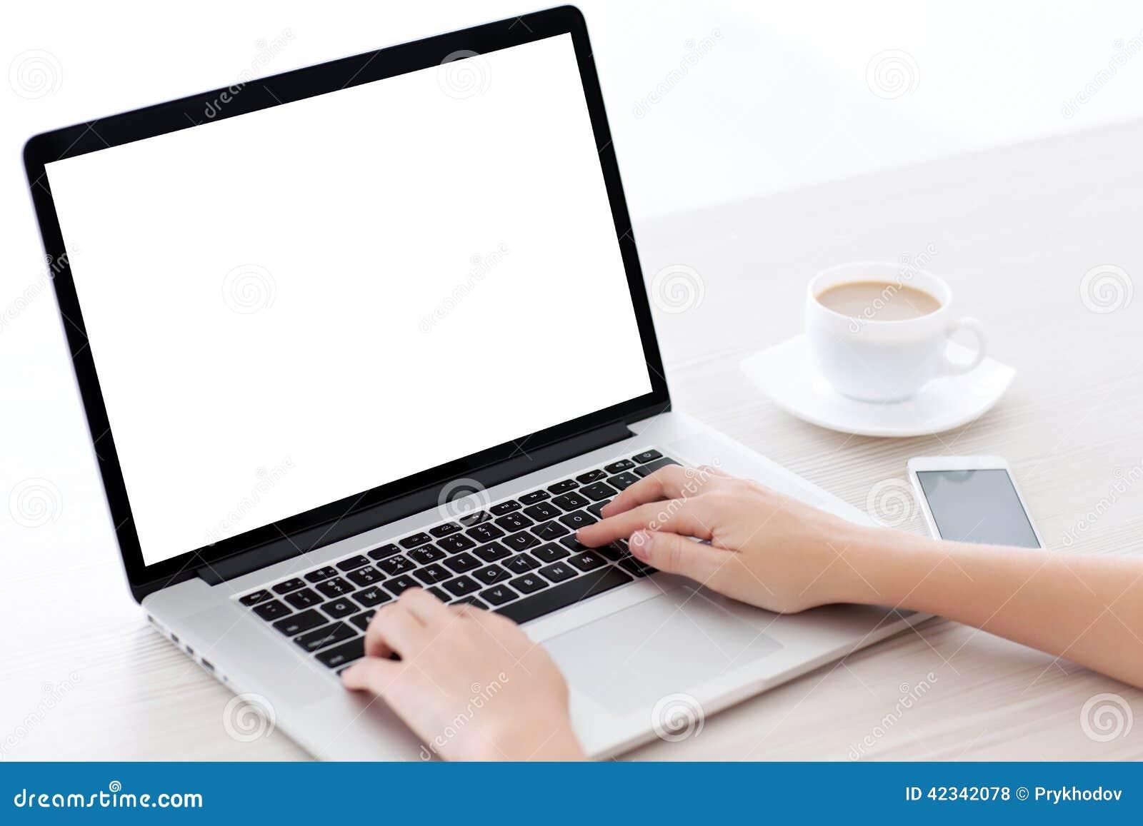 Mãos fêmeas que datilografam em um teclado do portátil com tela dentro