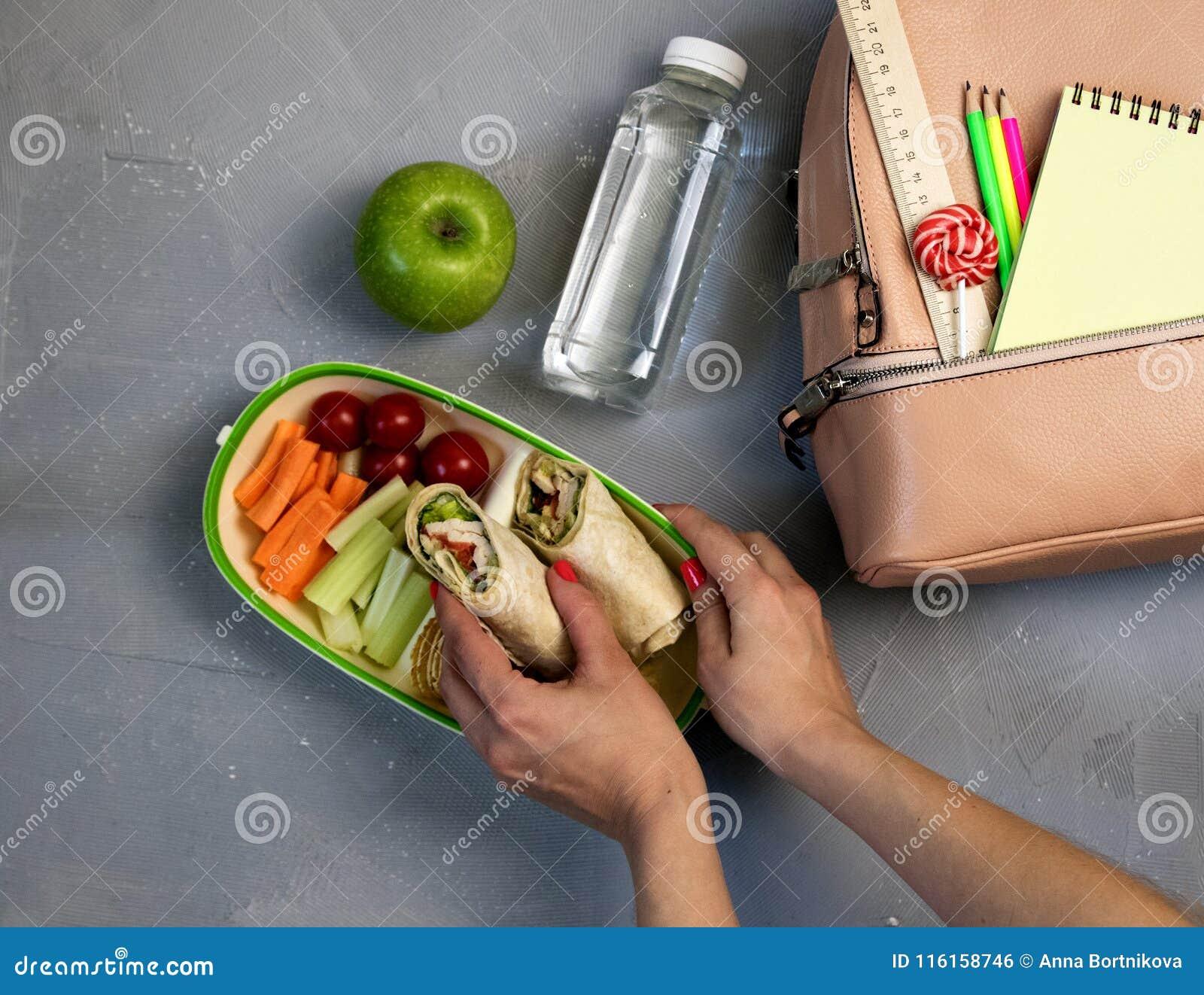Mãos fêmeas que embalam o jantar na cesta de comida na tabela cinzenta