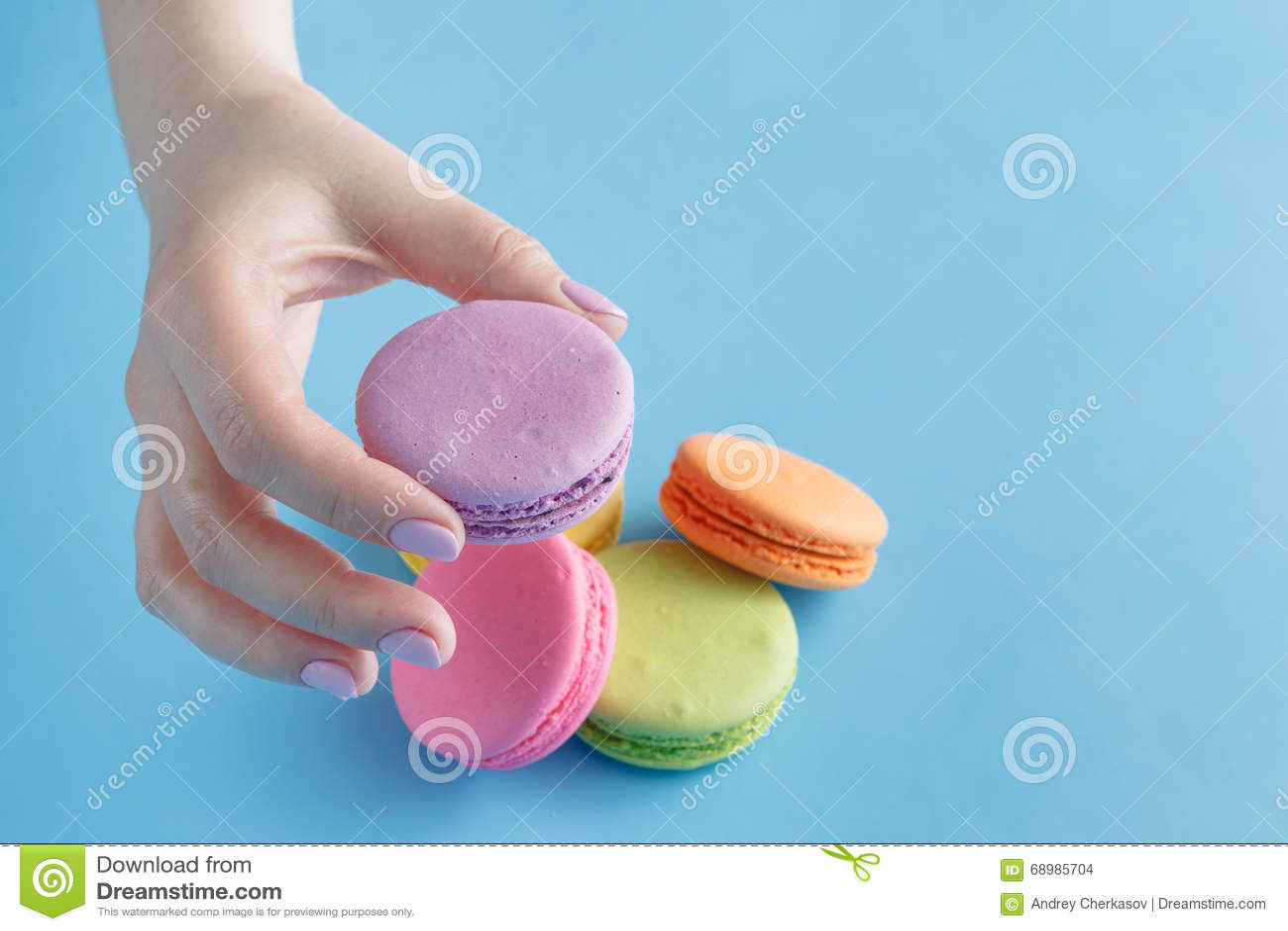 Mãos fêmeas que guardam bolinhos de amêndoa franceses coloridos