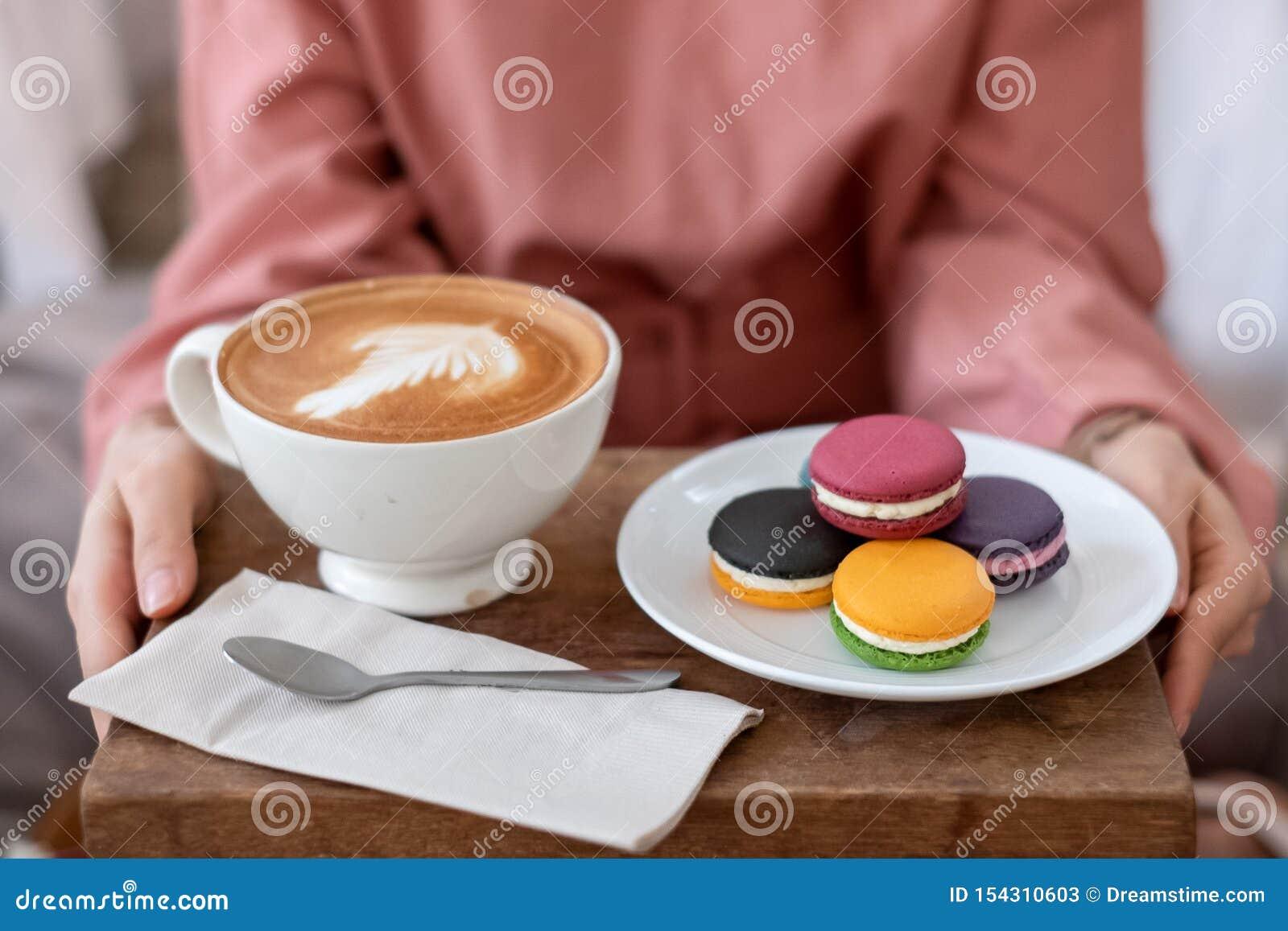 Mãos fêmeas que guardam bolinhos de amêndoa franceses coloridos e arte do latte