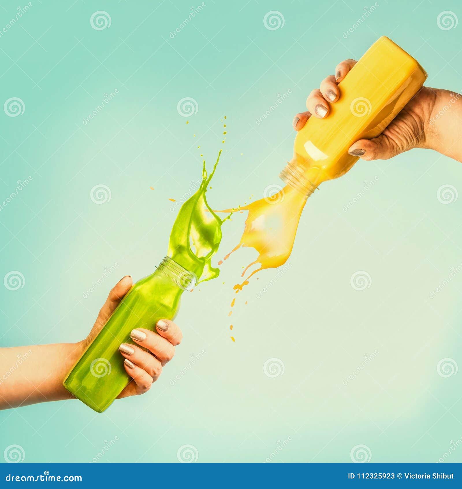 Mãos fêmeas que guardam garrafas com batido ou suco do respingo do amarelo e do verde no fundo azul com folhas e frutos tropicais
