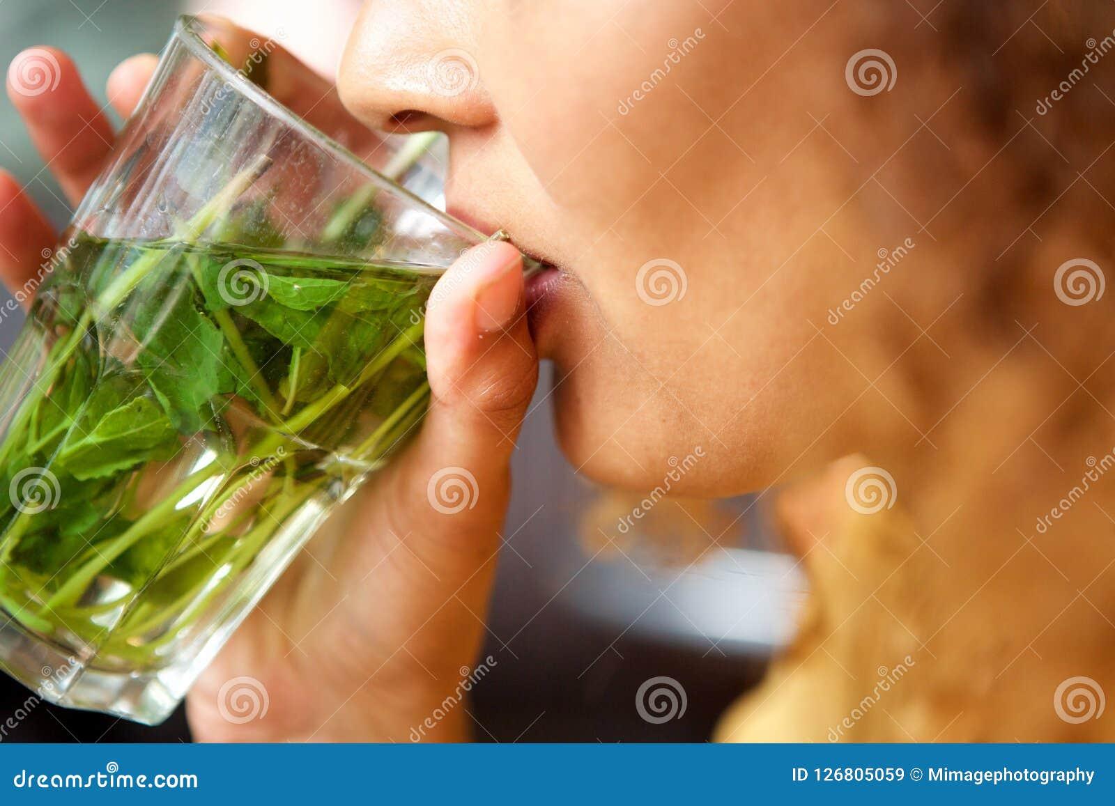 Mãos fêmeas que guardam o vidro do chá da hortelã à boca