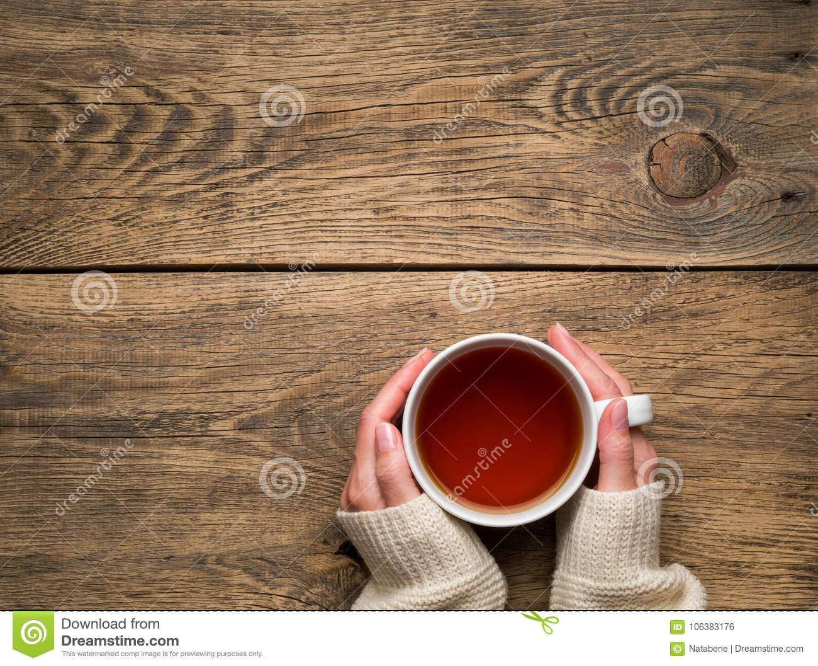 Mãos fêmeas que guardam uma caneca de chá preto quente inverno frio w branco