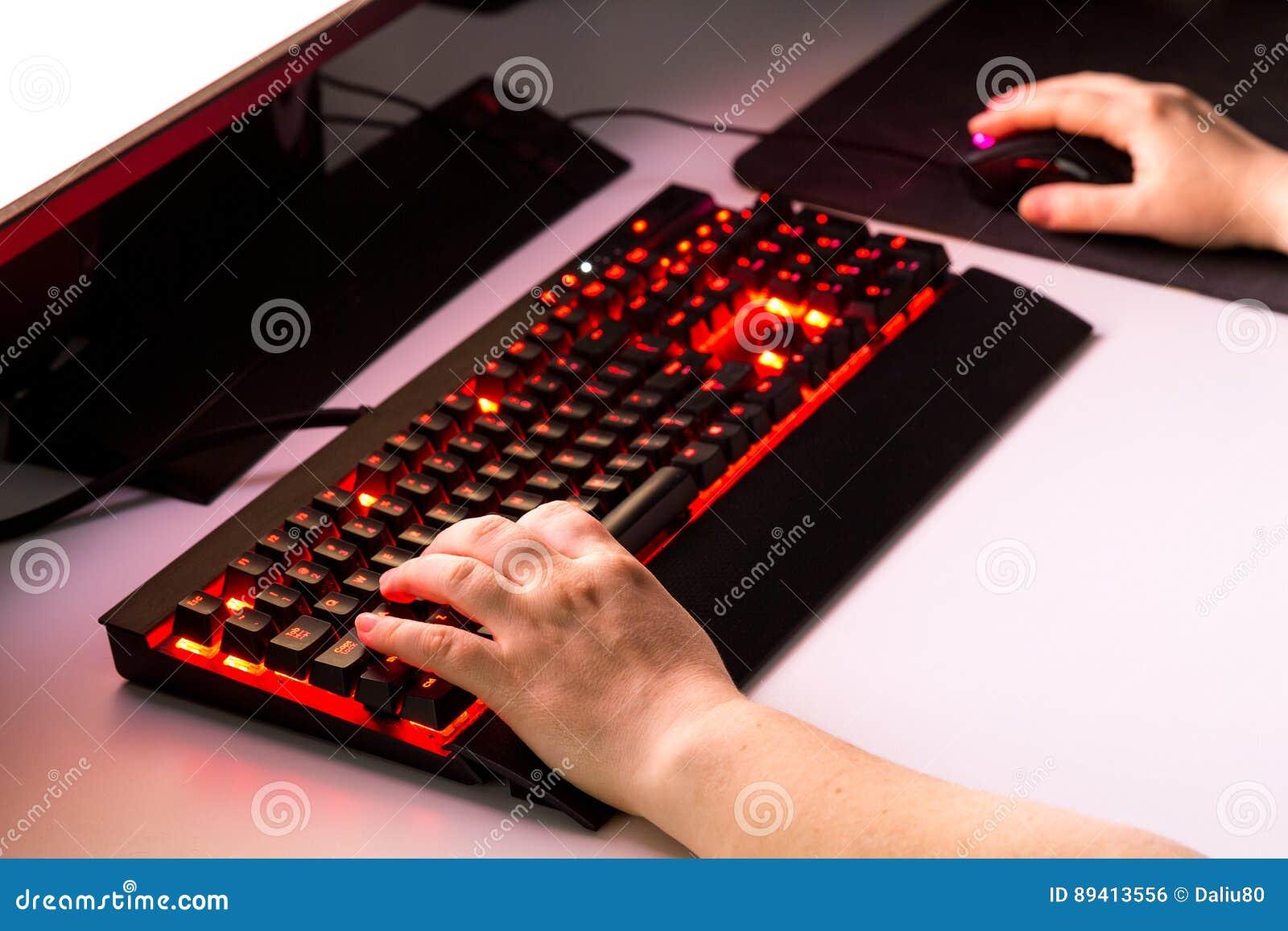 Mãos fêmeas que jogam o jogo de computador com engrenagem do jogo