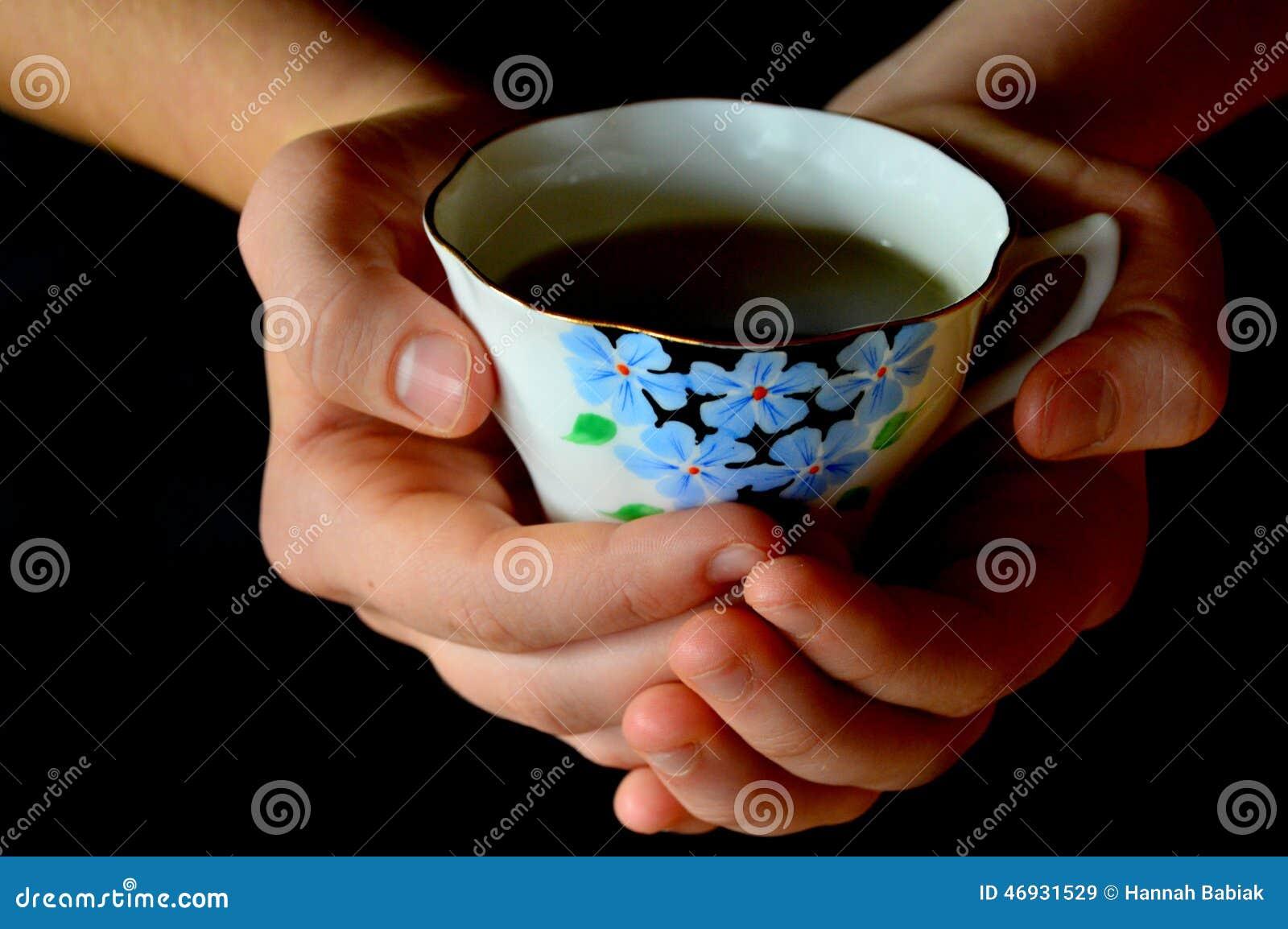 Mãos fêmeas que prendem um copo do chá