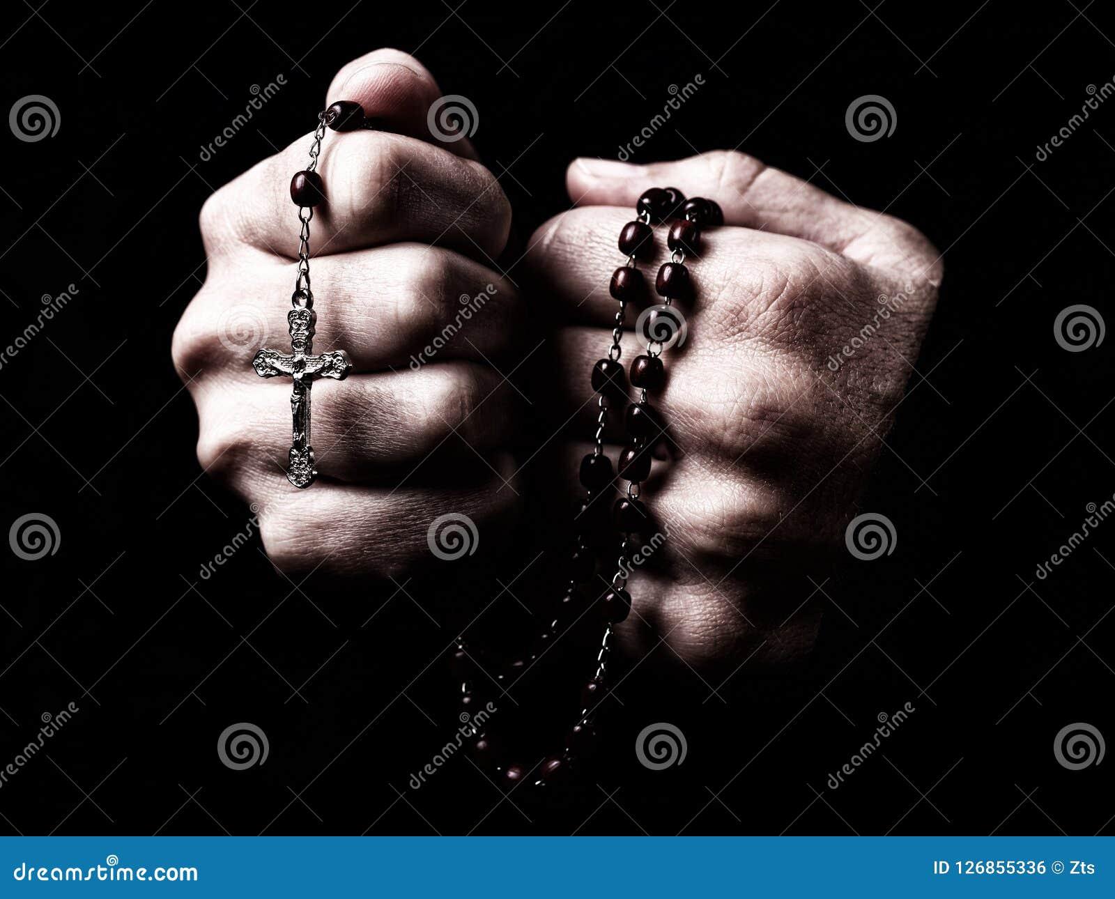 Mãos fêmeas que rezam guardando um rosário com Jesus Christ na cruz ou no crucifixo