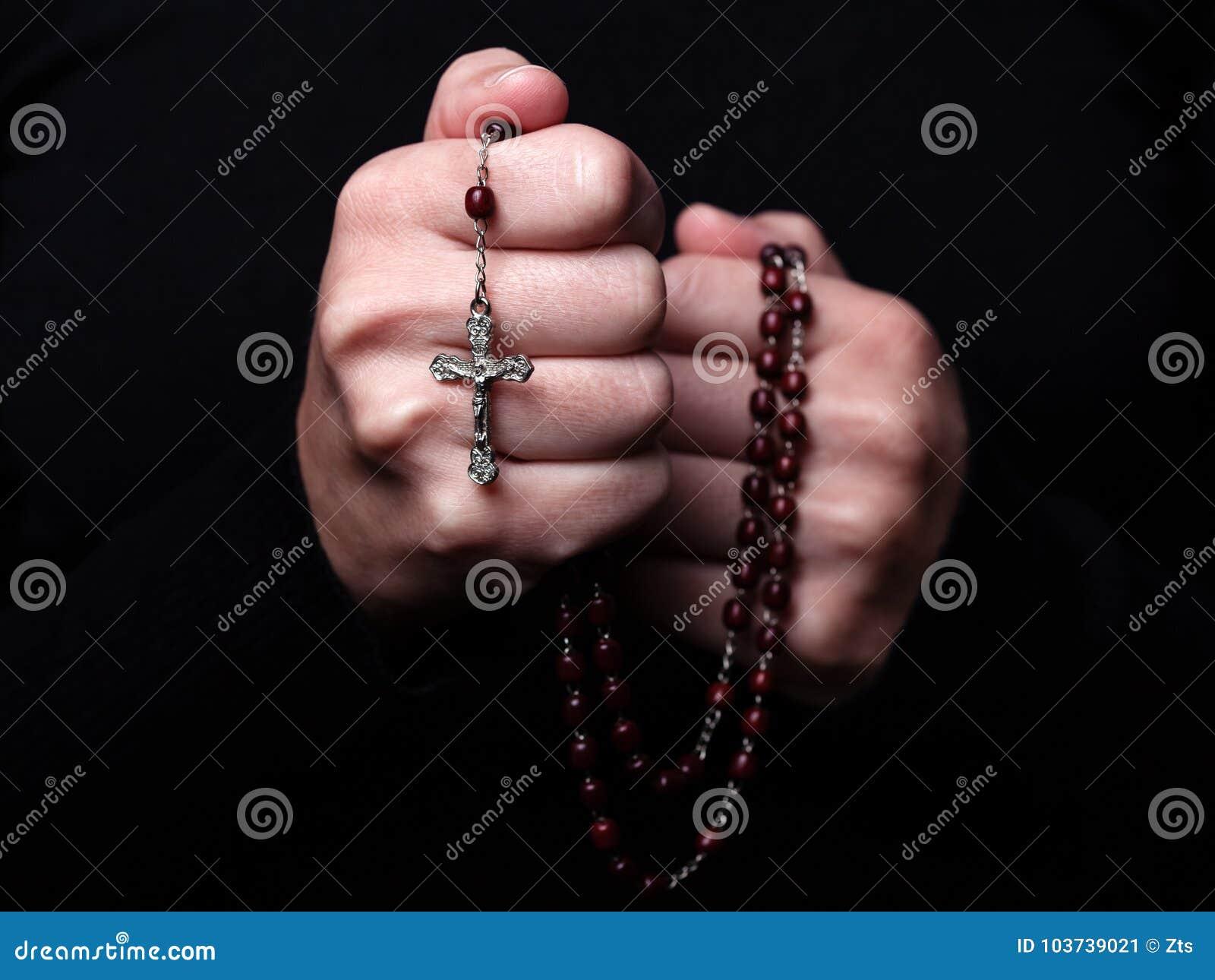Mãos fêmeas que rezam guardando um rosário com Jesus Christ na cruz ou no crucifixo no fundo preto