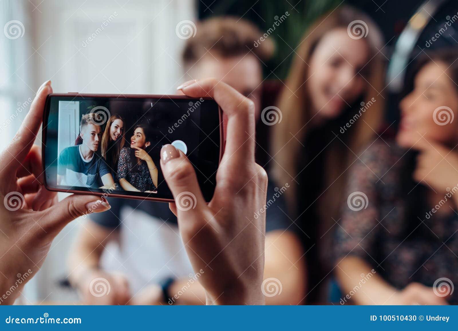 Mãos fêmeas que tomam a foto com o smartphone de amigos alegres novos, fundo borrado