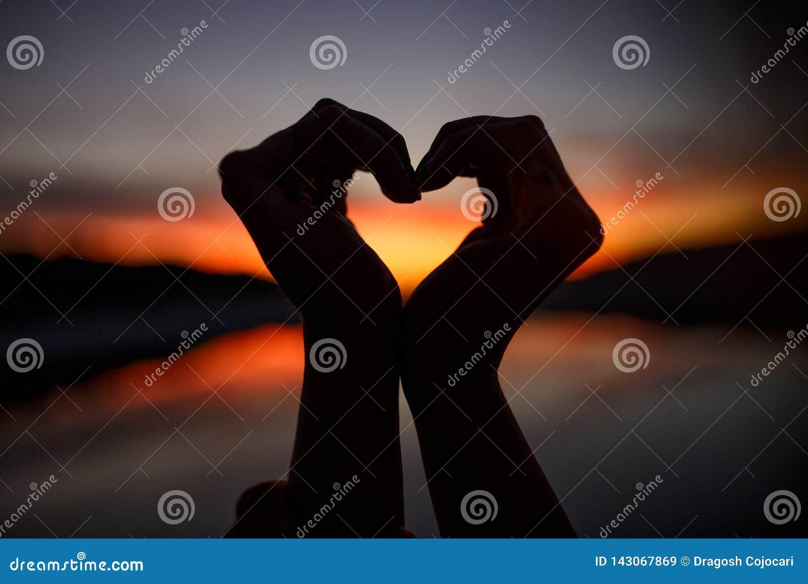 Mãos fêmeas sob a forma do coração no céu crepuscular e alaranjado Vista horizontal