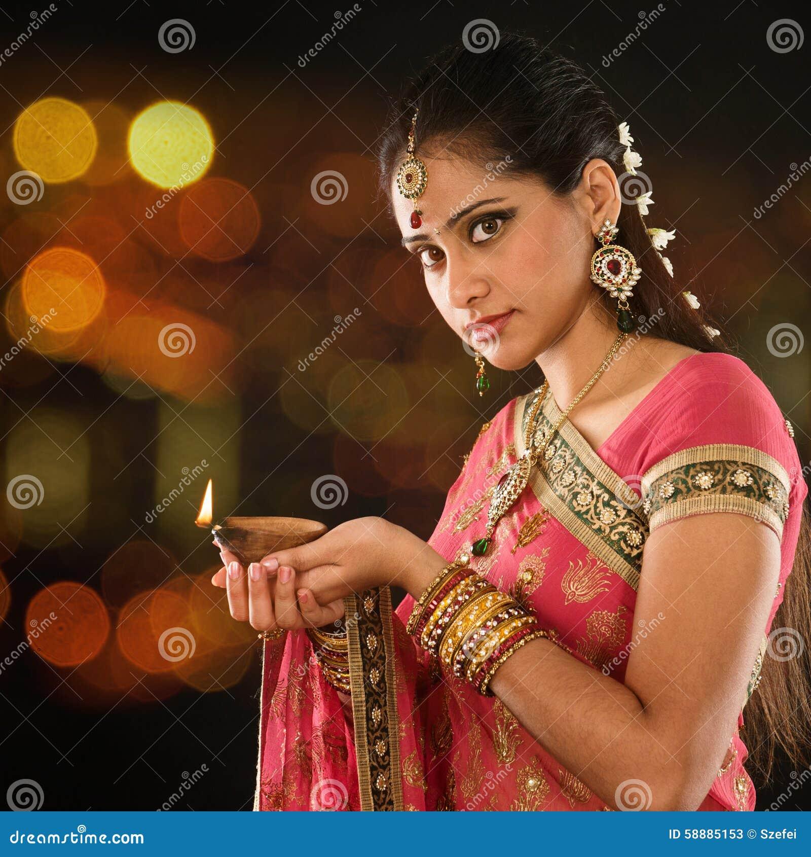 Mãos indianas da menina que guardam luzes do diya