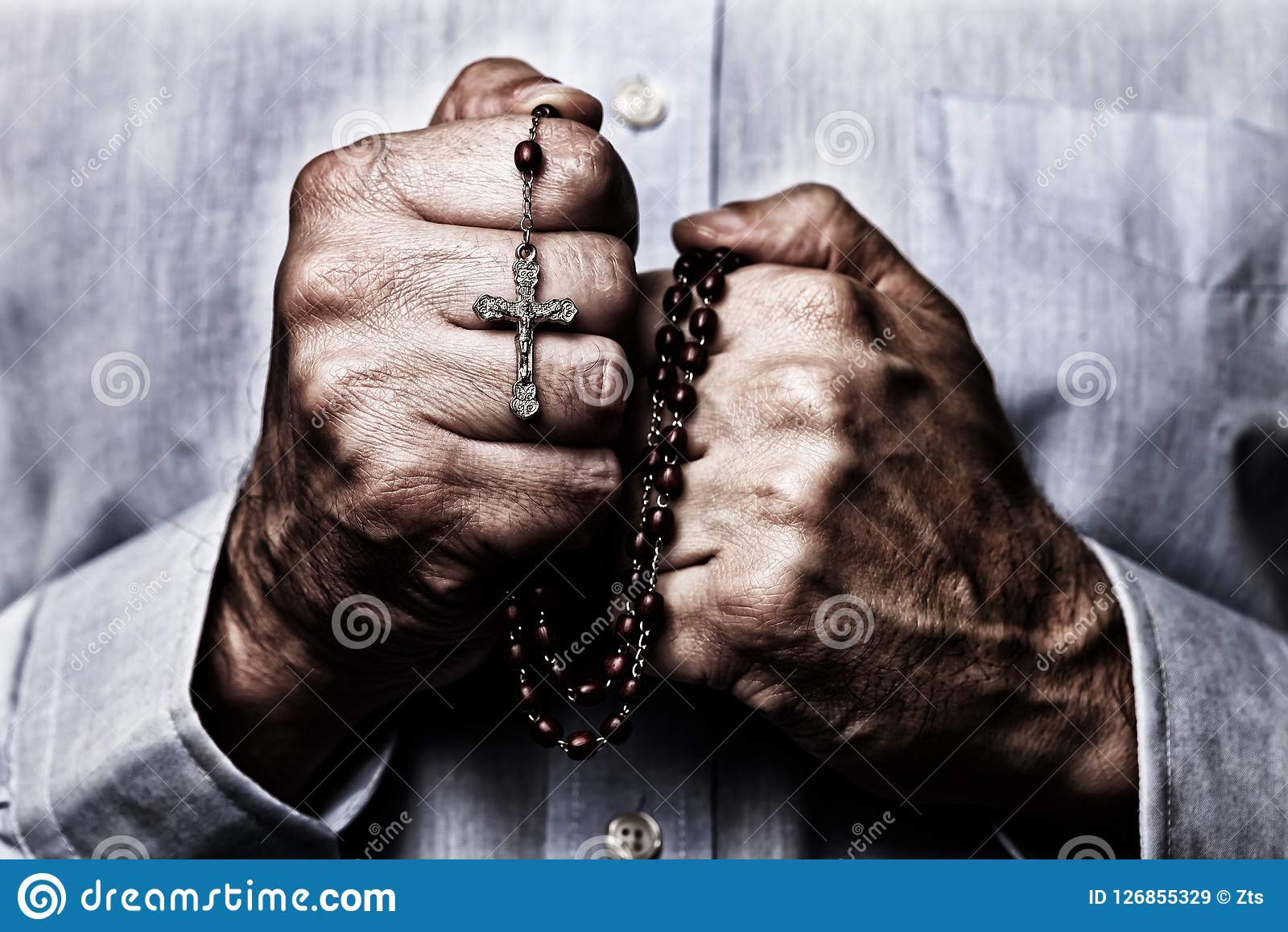 Mãos masculinas afro-americanos que rezam guardando um rosário dos grânulos com Jesus Christ na cruz ou no crucifixo