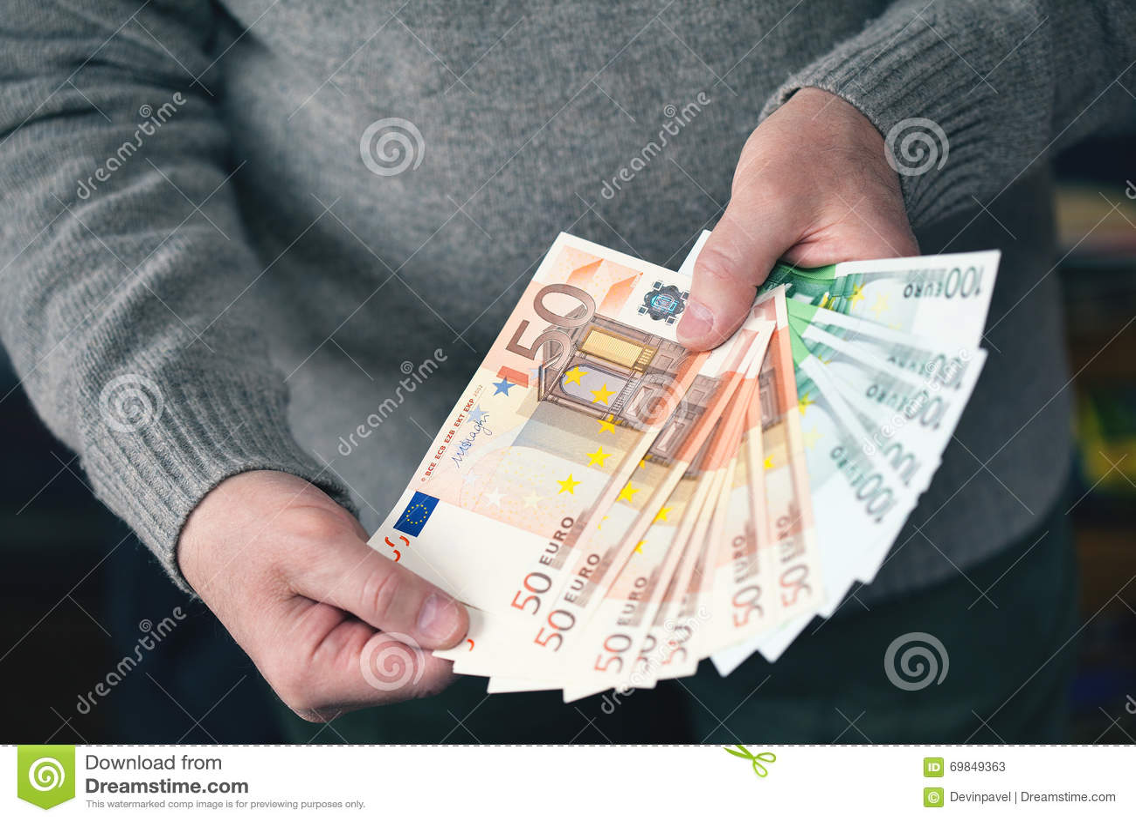 Mãos masculinas que guardam o dinheiro sob a forma de um fã Dinheiro, moeda do Euro