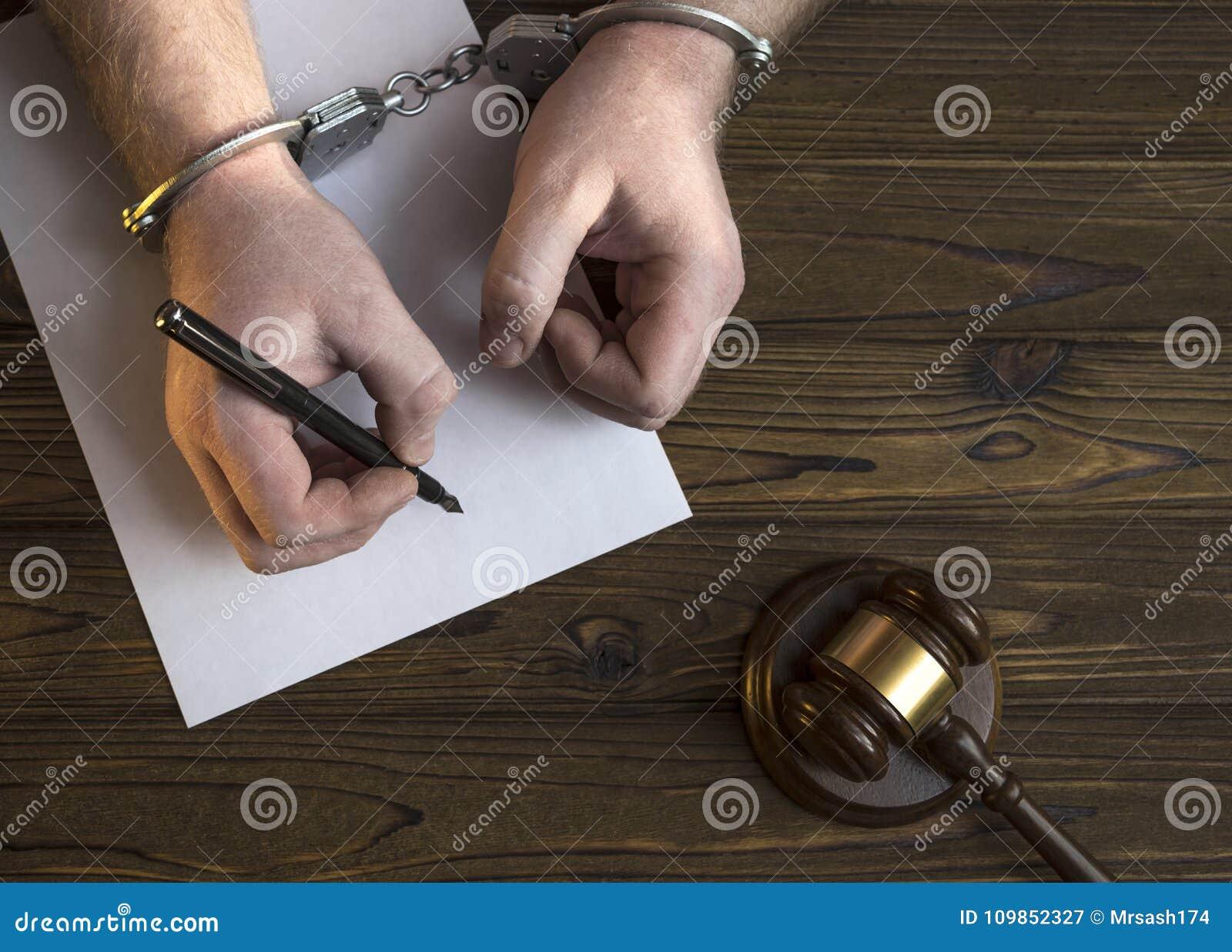 Mãos nas algemas e em um martelo do juiz