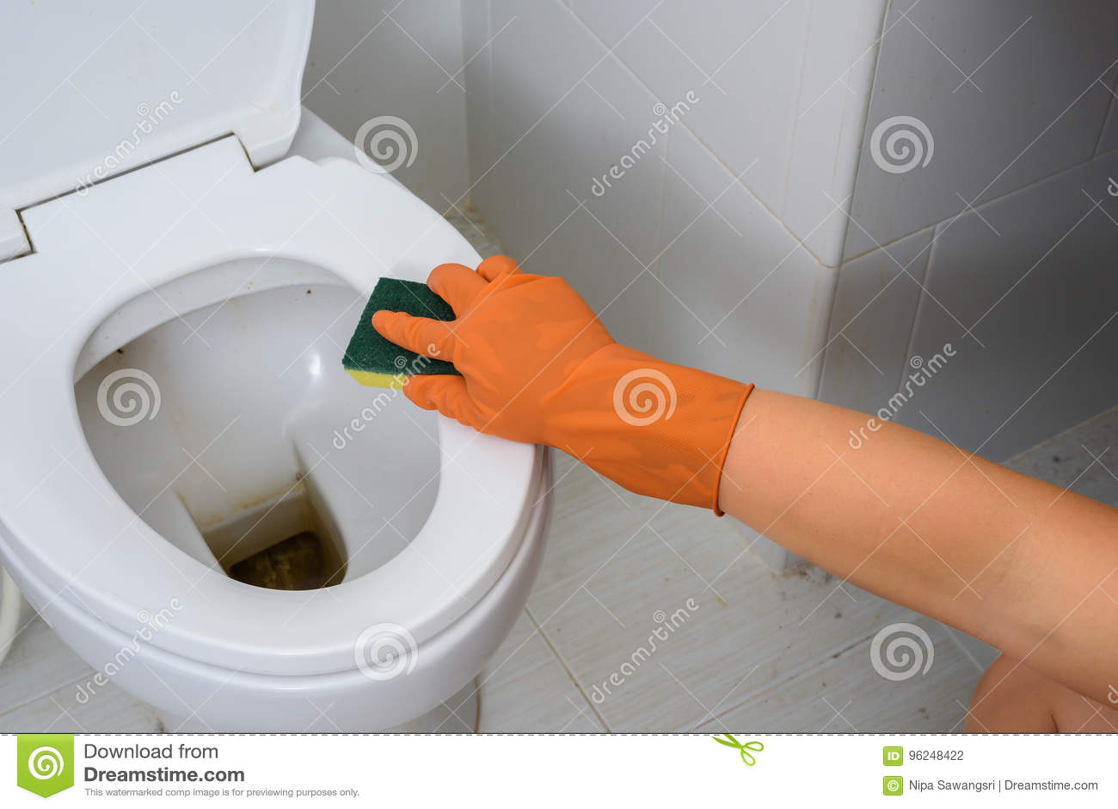 Mãos nas luvas alaranjadas que limpam WC, toalete, lavabos