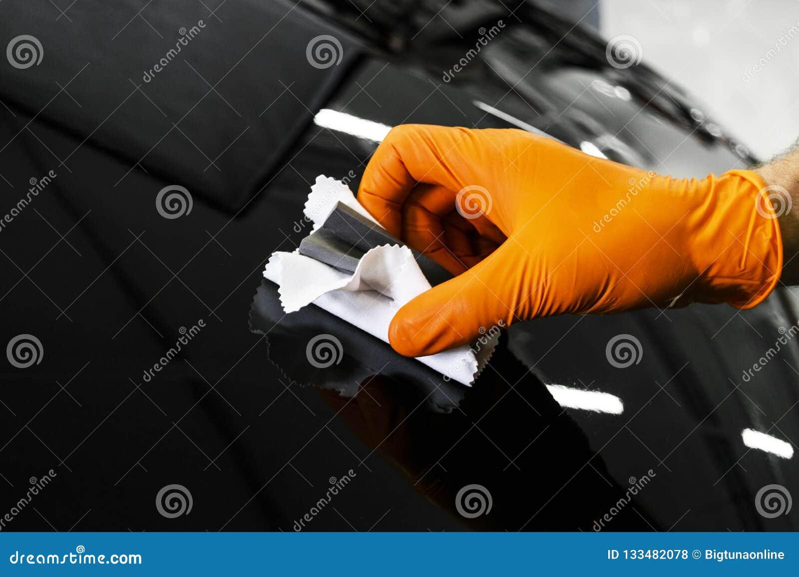 Mãos polonesas do trabalhador da cera do carro que lustram o carro Veículo lustrando e de lustro Detalhe do carro O homem guarda