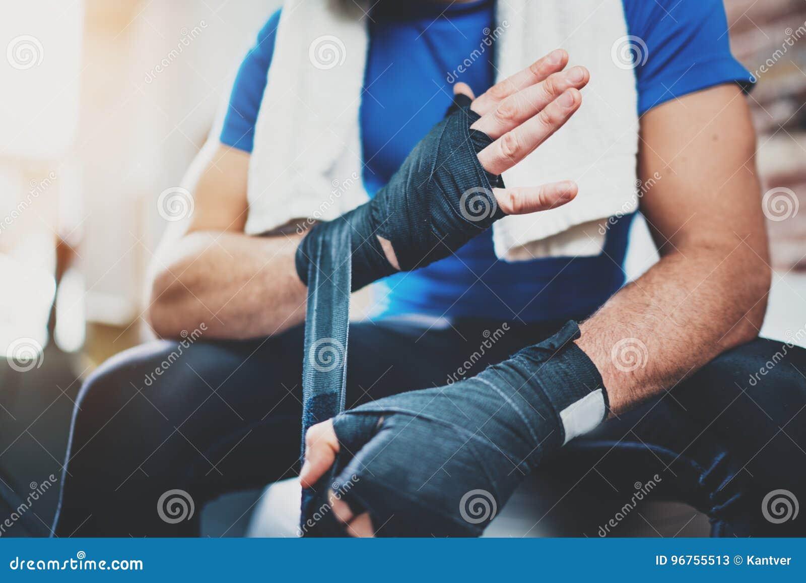 Mãos prepairing do homem muscular do pugilista para a sessão de formação kickboxing dura no gym Atleta novo que amarra o encaixot