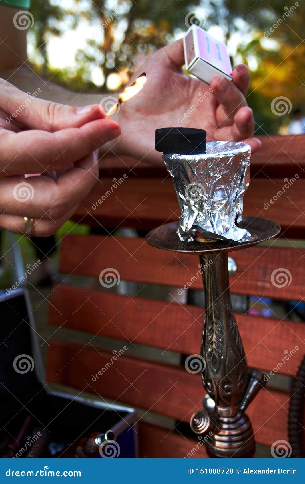 Mãos que guardam fósforos e carvão ardente para o cachimbo de água no parque
