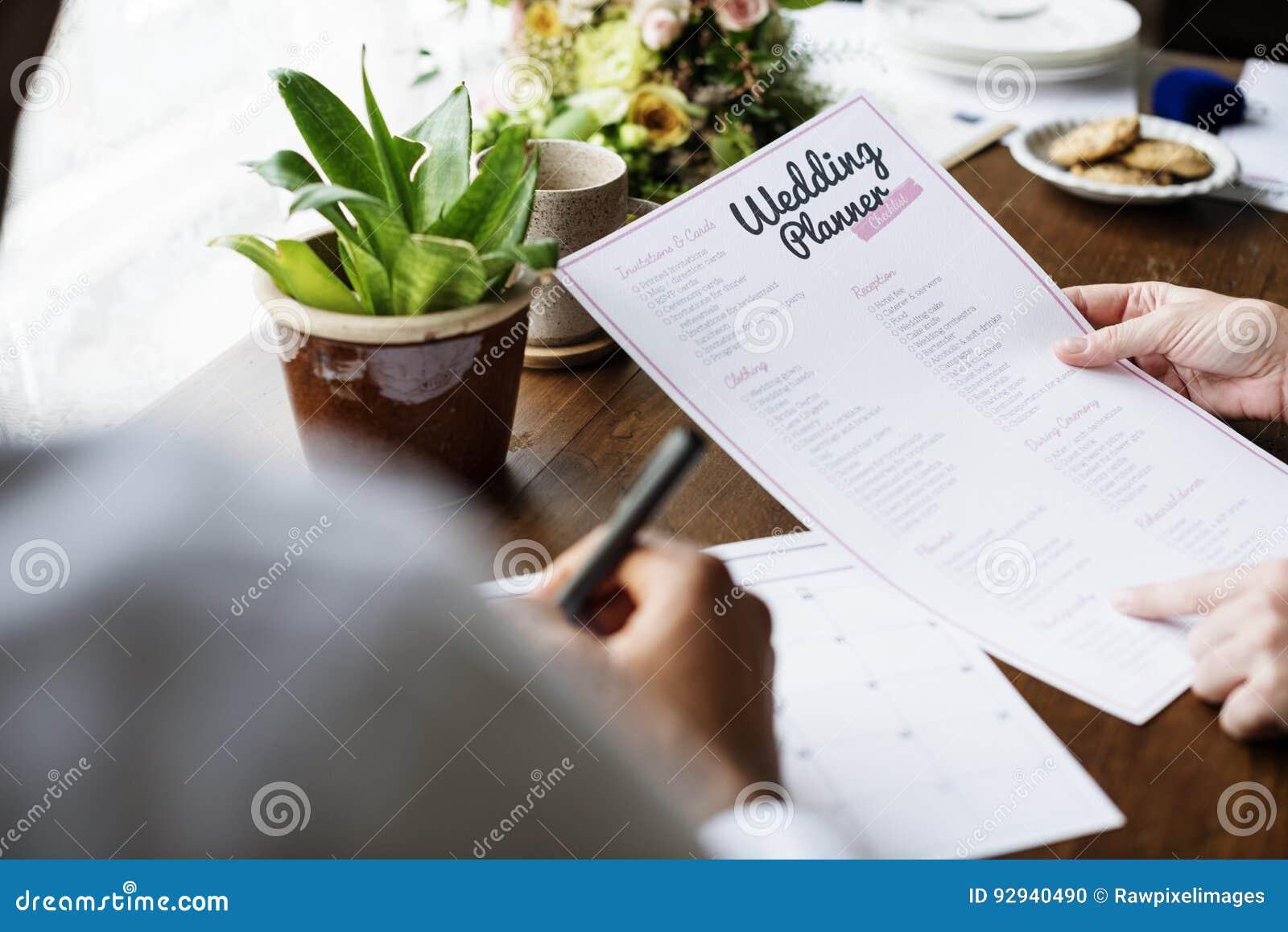 Mãos que guardam o planejador Checklist Information Preparation do casamento