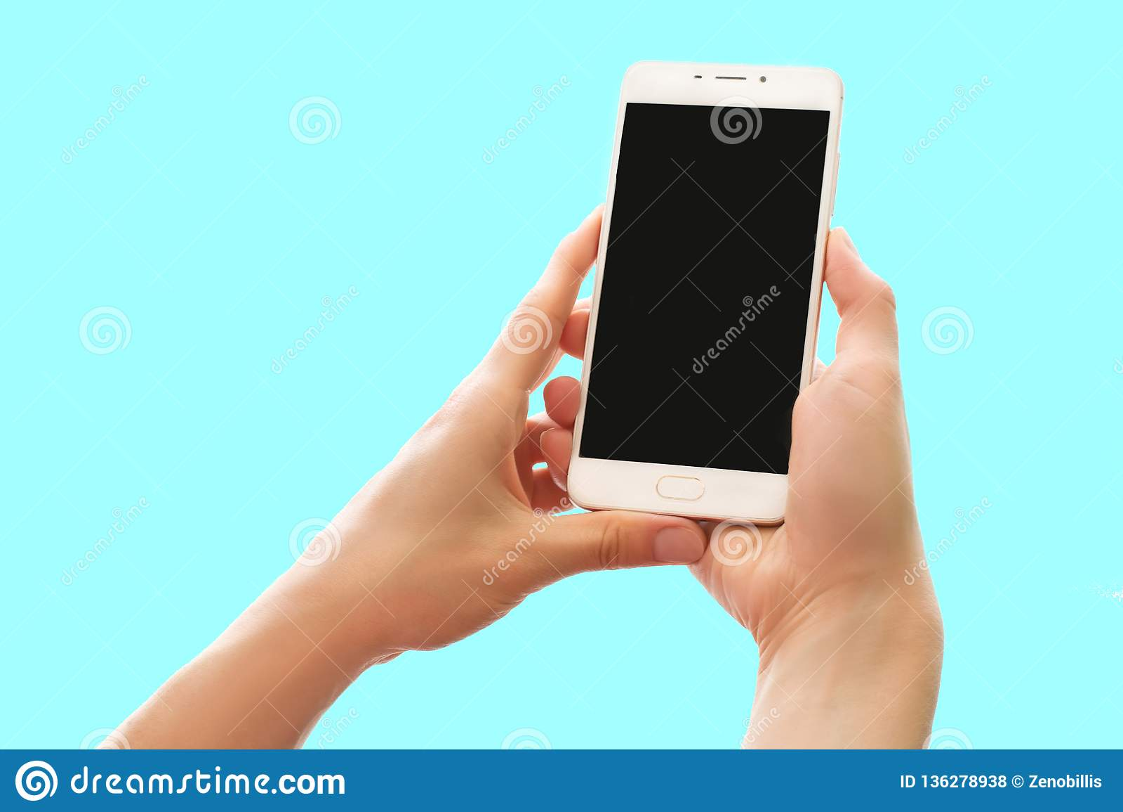 Mãos que guardam o smartphone com a tela preta isolada no fundo azul pastel