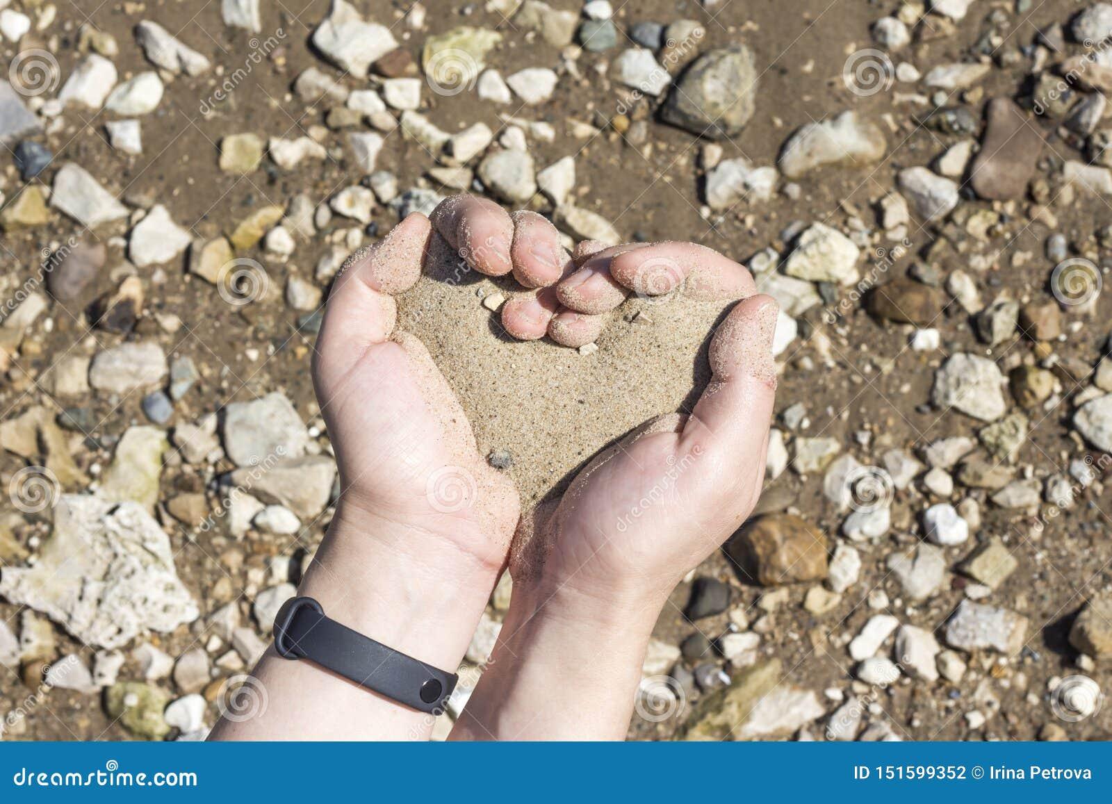 Mãos que guardam uma areia nas palmas do coração, o conceito de vida que corre para fora como a areia através dos dedos