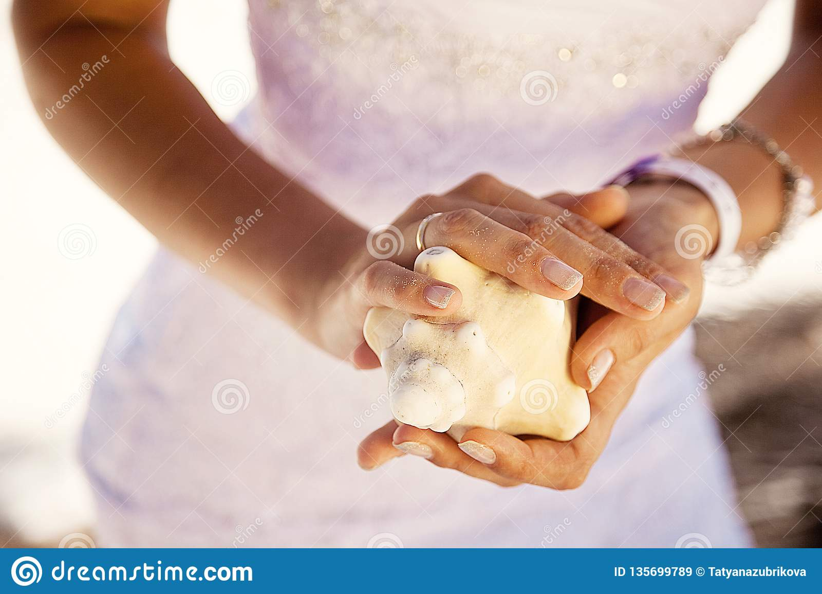 Mãos que guardam uma concha do mar, fundo tropical