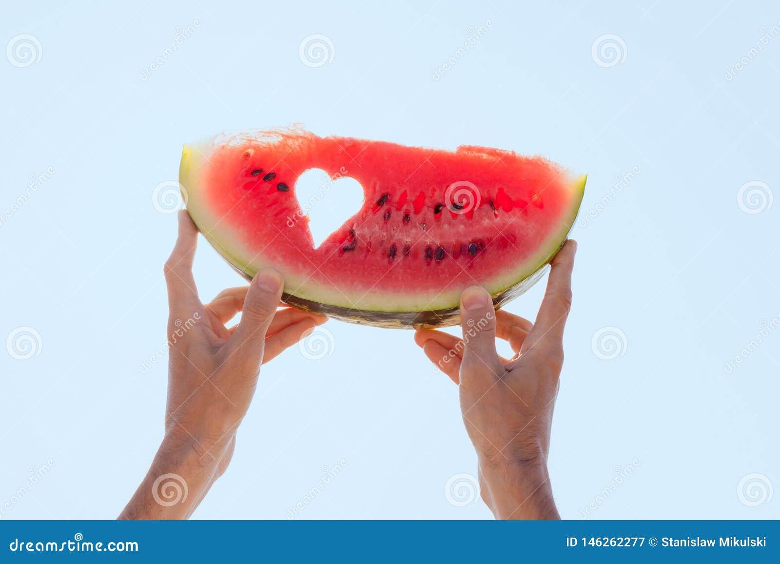 M?os que guardam uma fatia da melancia com centro do cora??o para o c?u