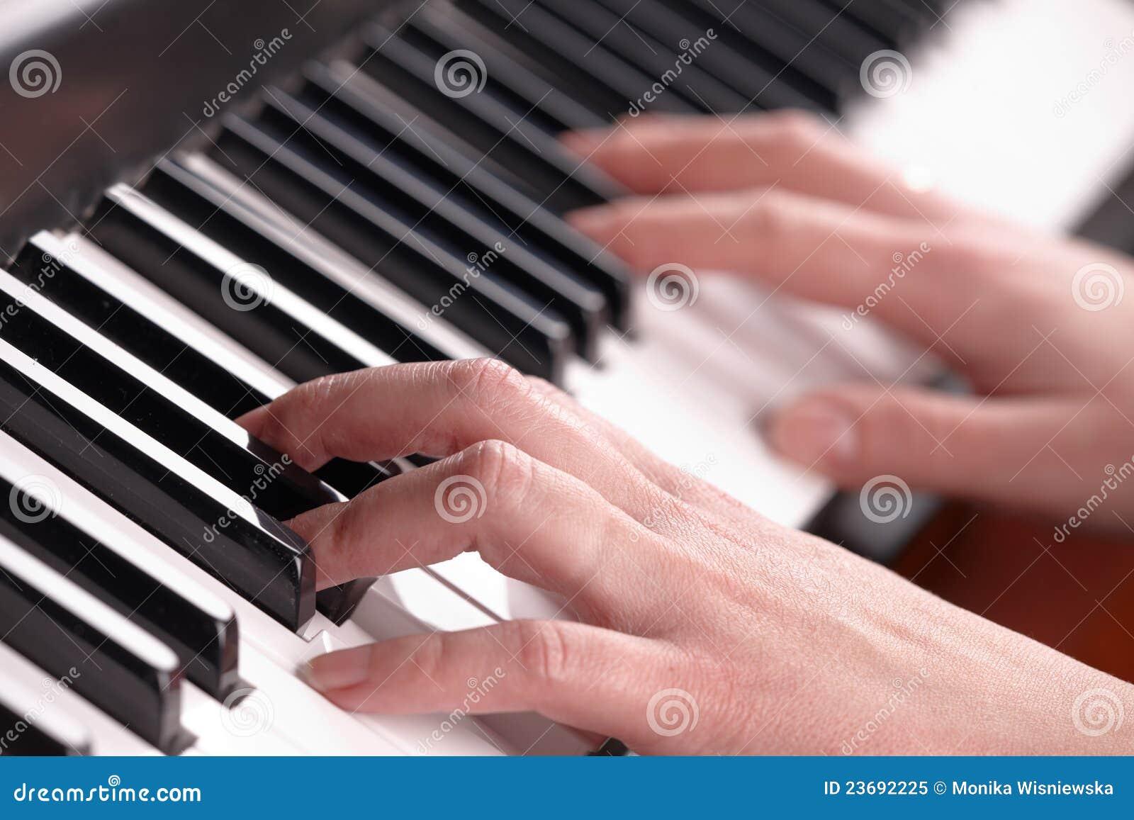 Mãos que jogam a música no piano