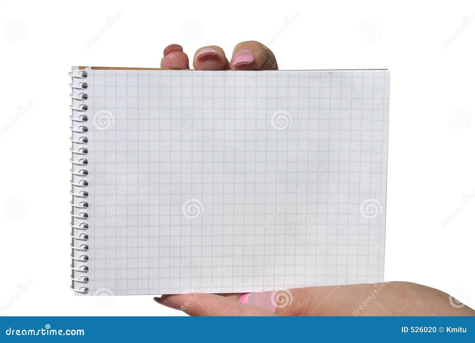 Mãos que prendem o caderno espiral em branco
