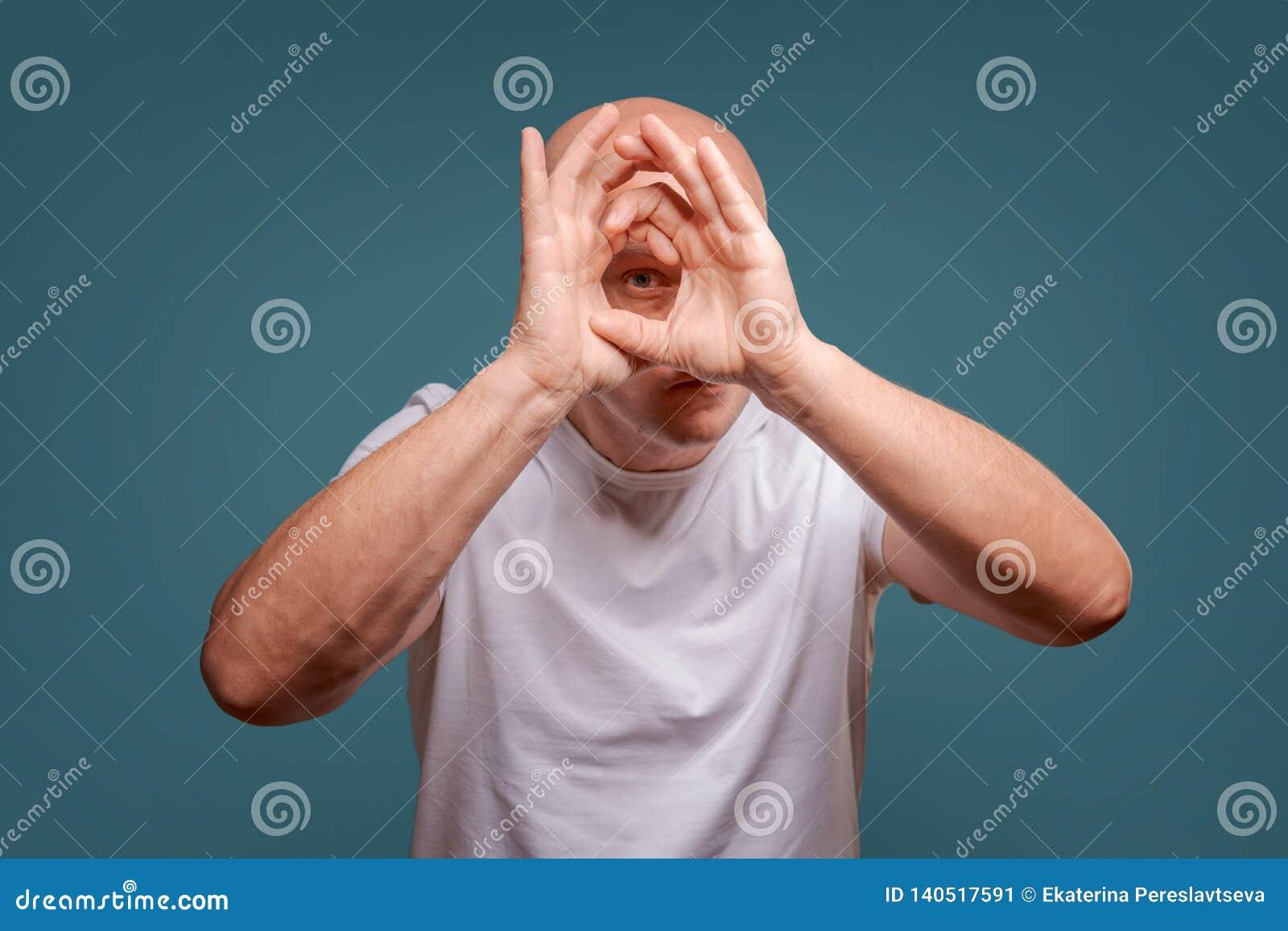 Mężczyzna na błękitnym tle w mienie rękach blisko jego oczu jak teleskop Podpatruje