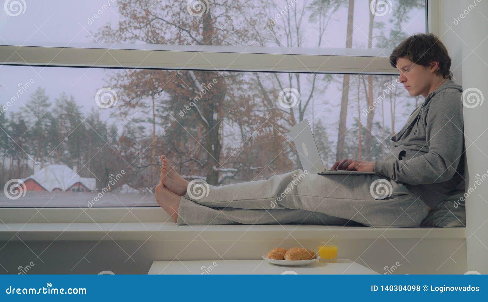 Mężczyzna obsiadanie na nadokiennym parapetu use laptopie