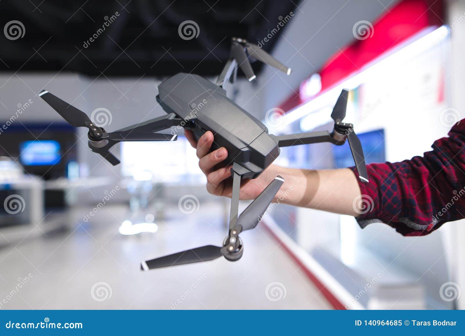 Mężczyzna ręka trzyma quadcopter w tle elektronika sklep Nabywa dron w narzędzia sklepie