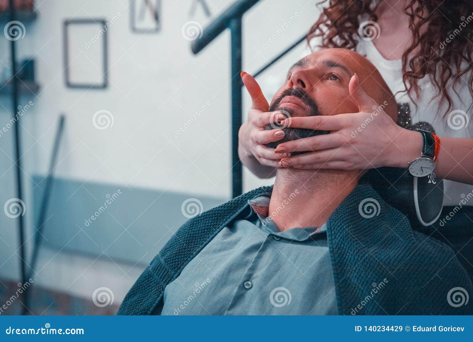 Mężczyzna w fryzjera męskiego sklepie dla fachowej traktowanie brody i włosy
