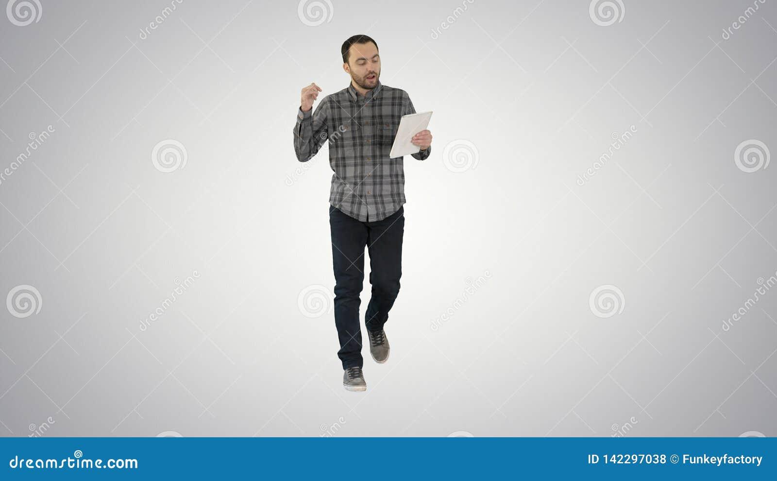 Mężczyzna w przypadkowym odprowadzeniu z pastylką i opowiadać przez wideokonferencji na gradientowym tle