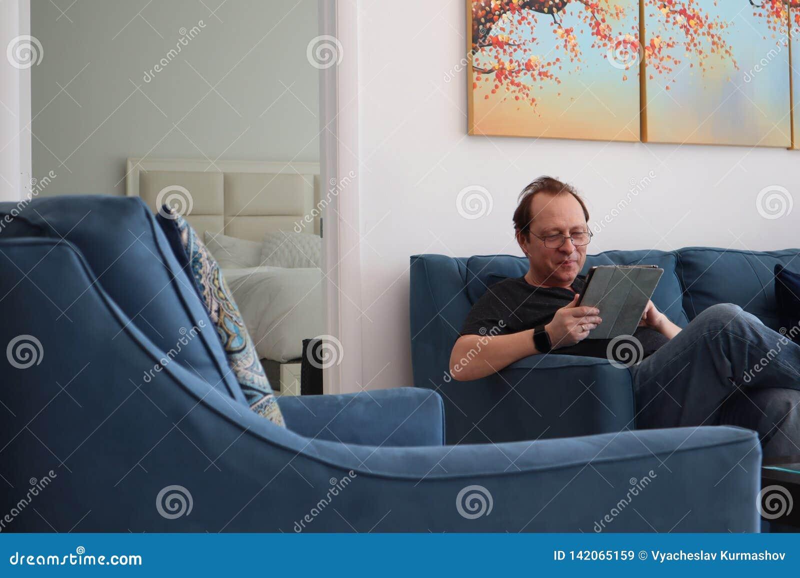 Mężczyzna z szkłami pracuje na pastylce obsługuje relaksować w izbowym obsiadaniu na leżance Zainteresowany atrakcyjny mężczyzny