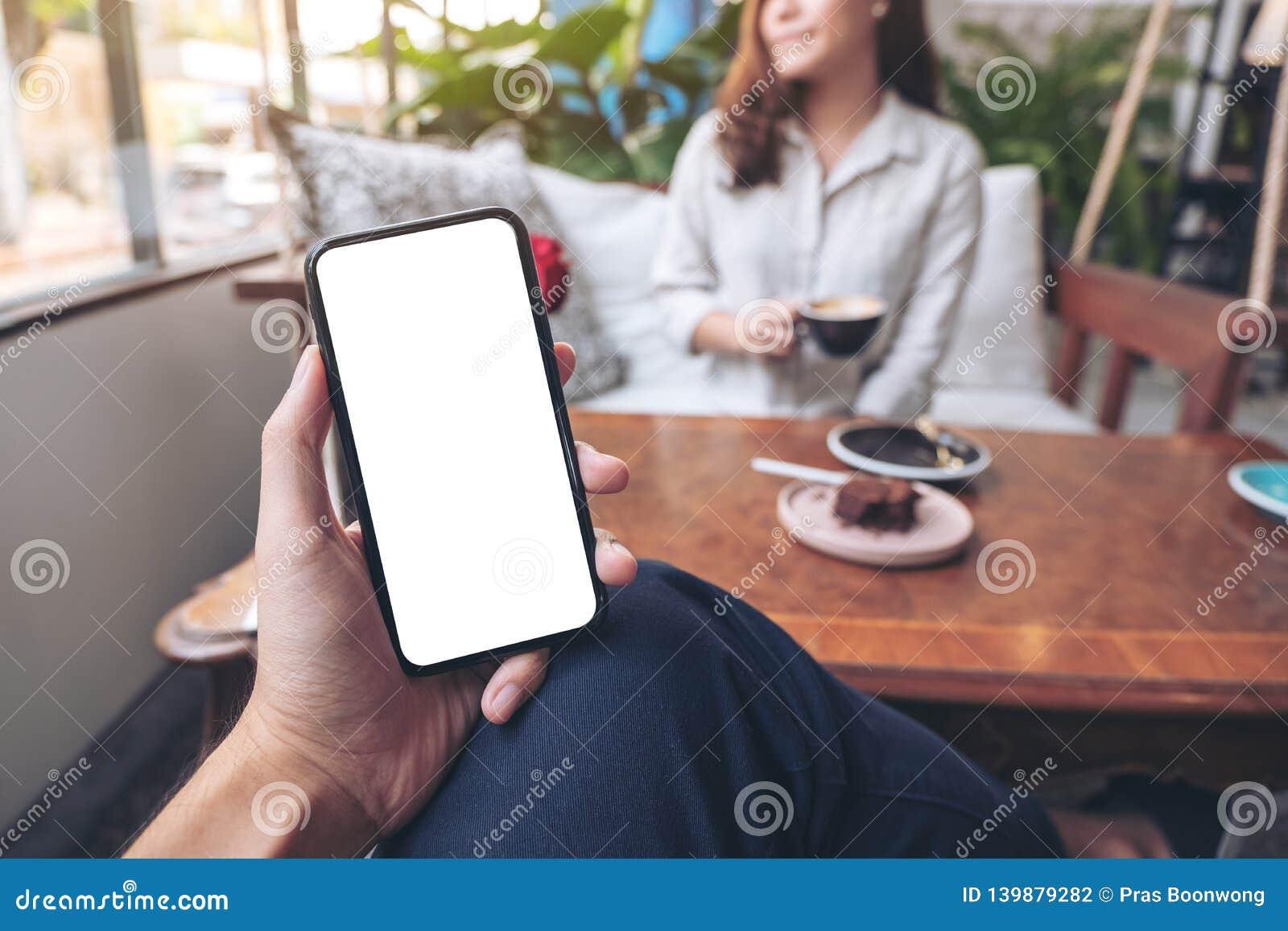 Mężczyzny ręka trzyma czarnego telefon komórkowego z pustym bielu ekranem z kobiety obsiadaniem w kawiarni