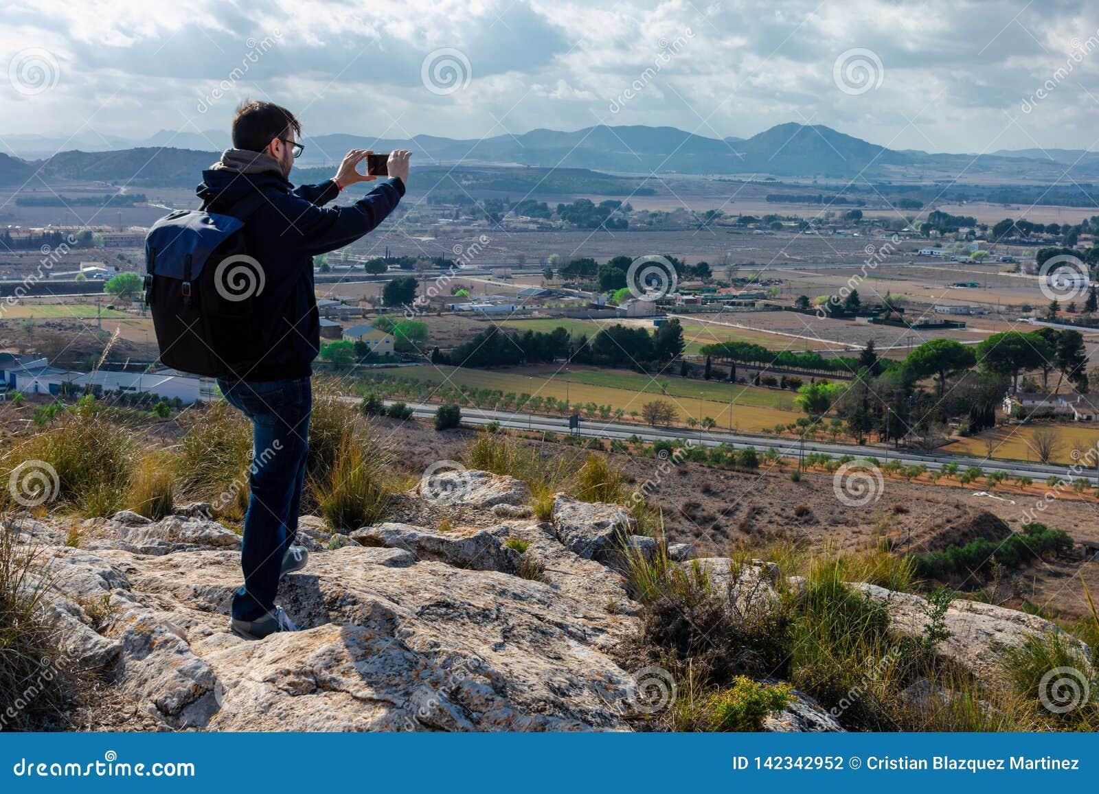 Męski turysta bierze fotografię z telefon komórkowy kamerą