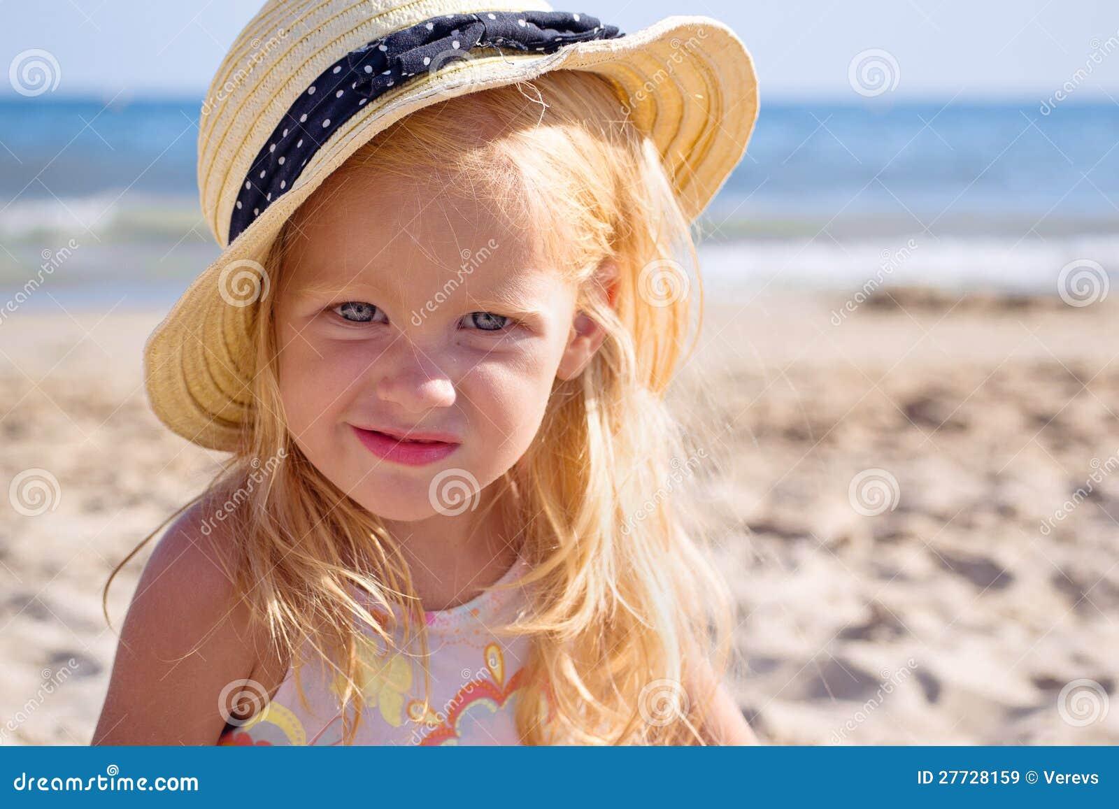 Mädchen auf dem Strand, der einen Hut trägt