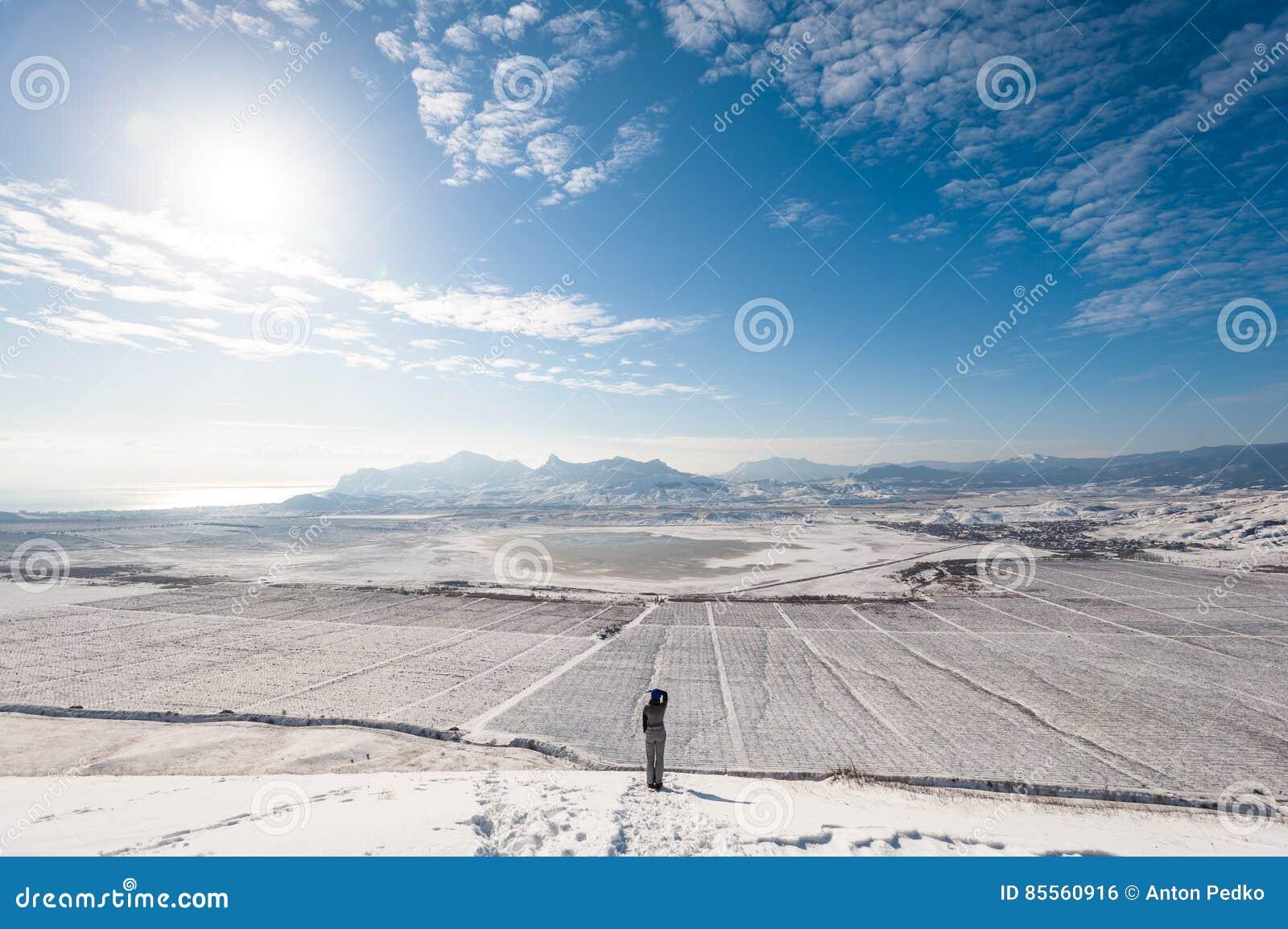 Mädchen auf der schneebedeckten Steigung mit Bergen und das Meer auf Hintergrund