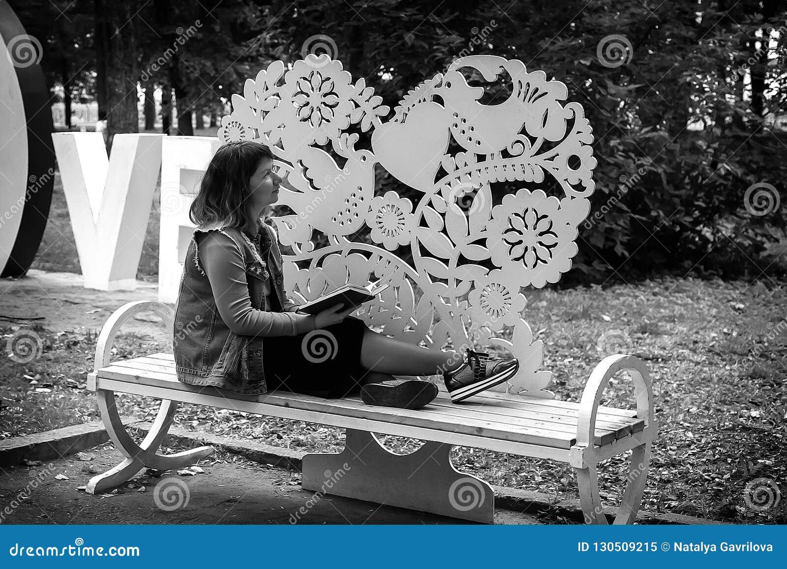 Mädchen auf einer Bank im Park mit einem Buch in ihren Händen, Schwarzweiss-Foto