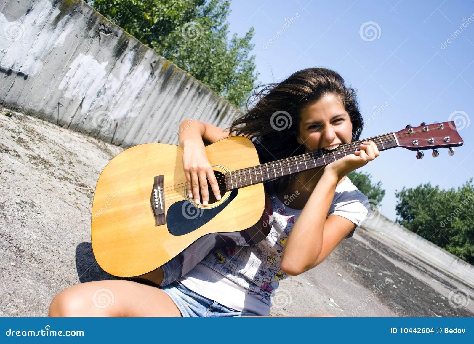 Mädchen beißt Gitarre