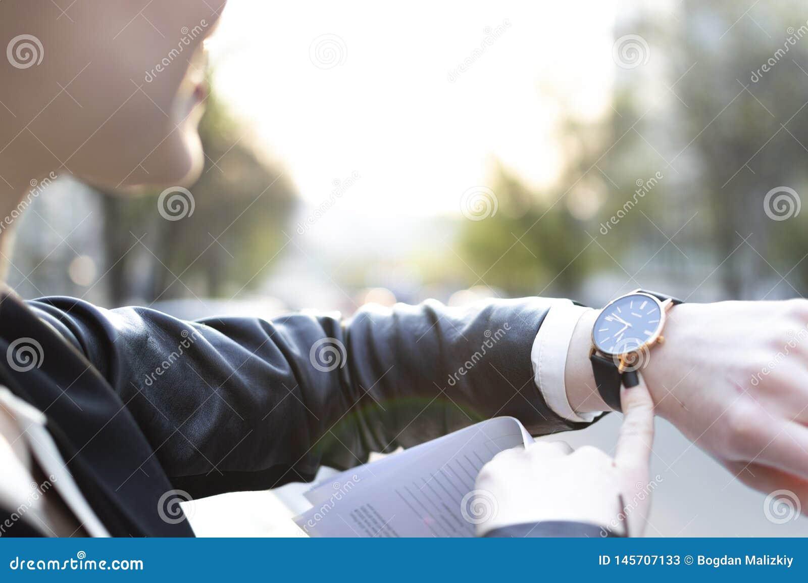 Mädchen betrachtet die Uhr, die Sonne glänzt in der Kamera