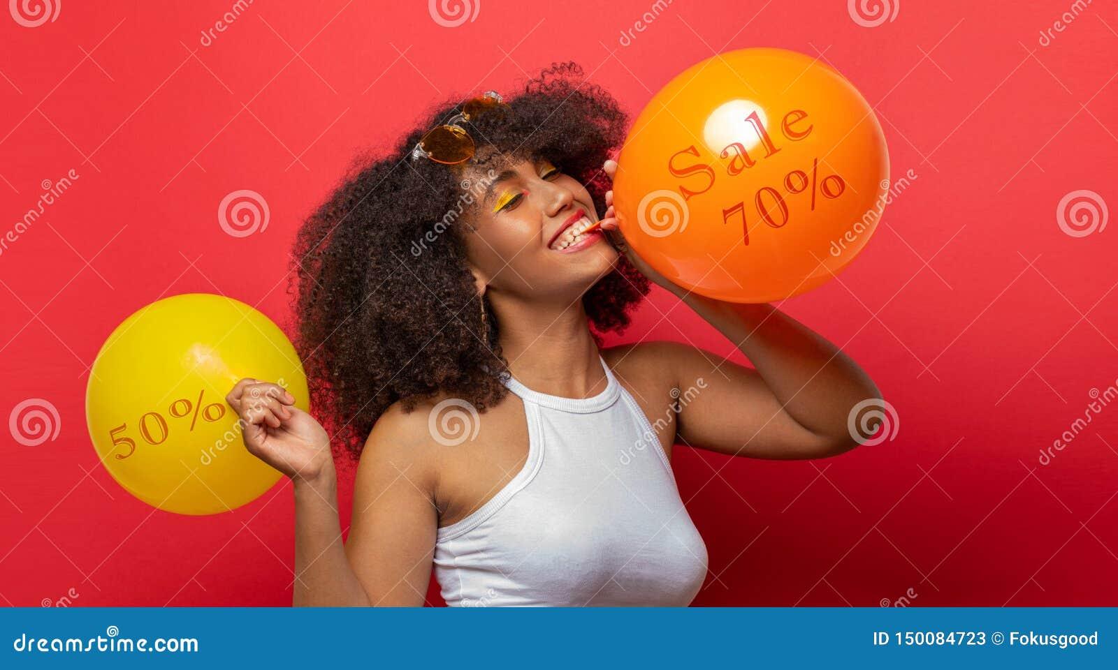 Mädchen bläst Ballone mit Rabatten auf