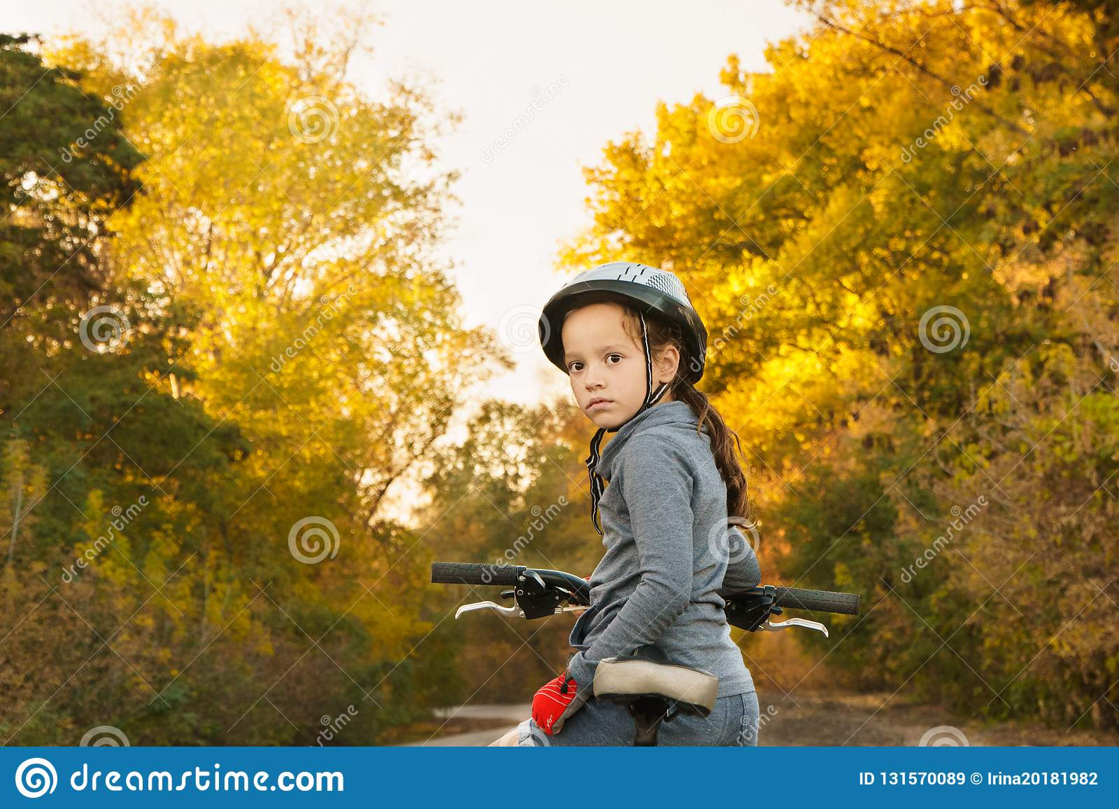 Mädchen, das auf dem Fahrrad sitzt Weg im Herbst Fahren auf die Straße