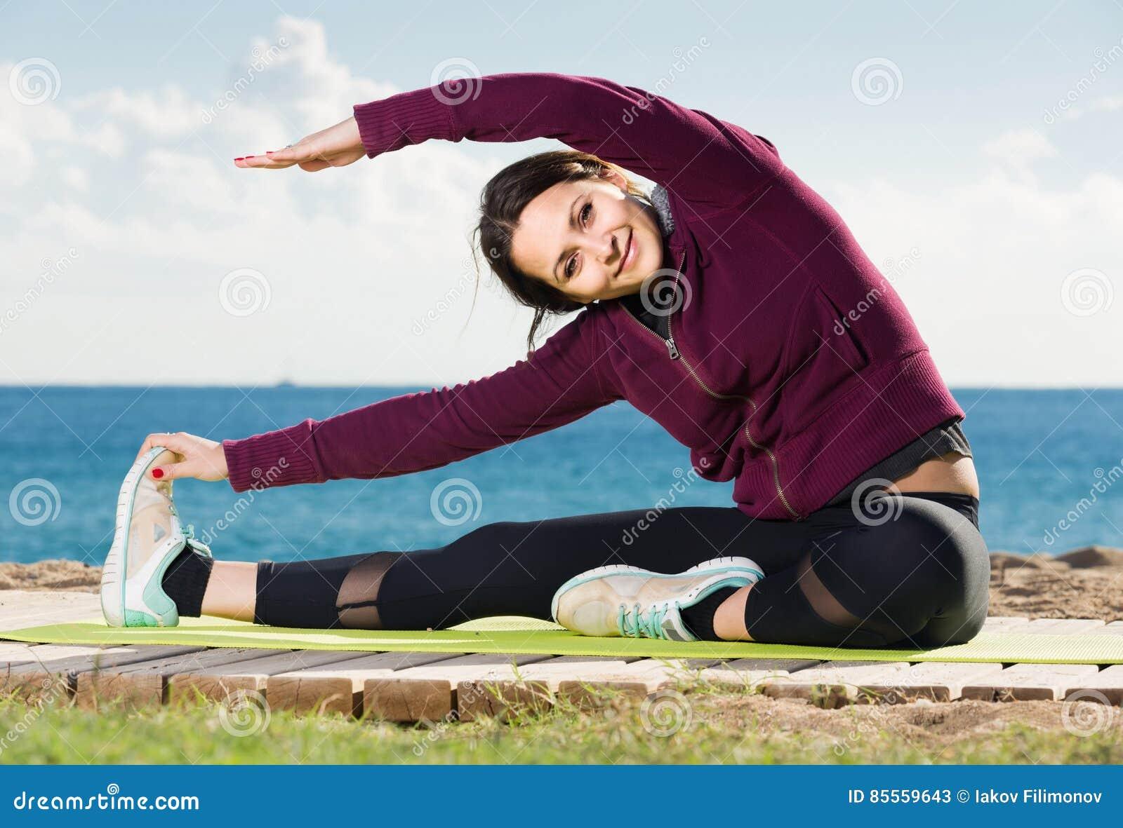 Mädchen, das auf der Übungsmatte im Freien trainiert