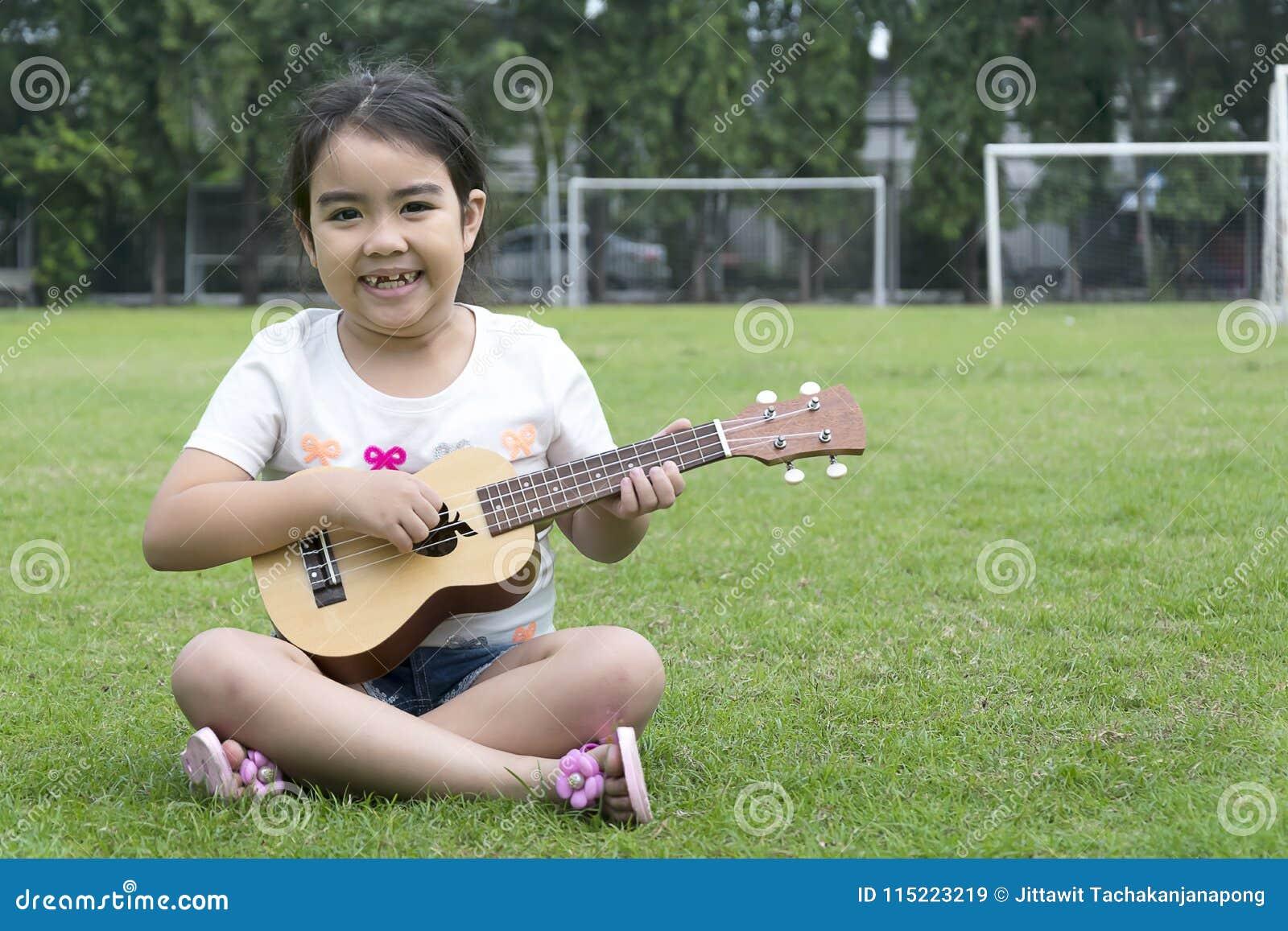 Mädchen, das auf Gras mit einem netten Lächeln spielt Ukulele sitzt
