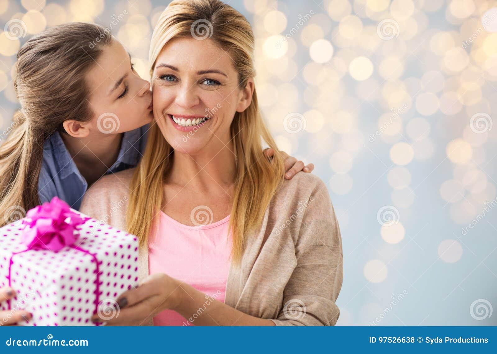 Mädchen, das der Mutter über Lichtern Geburtstagsgeschenk gibt