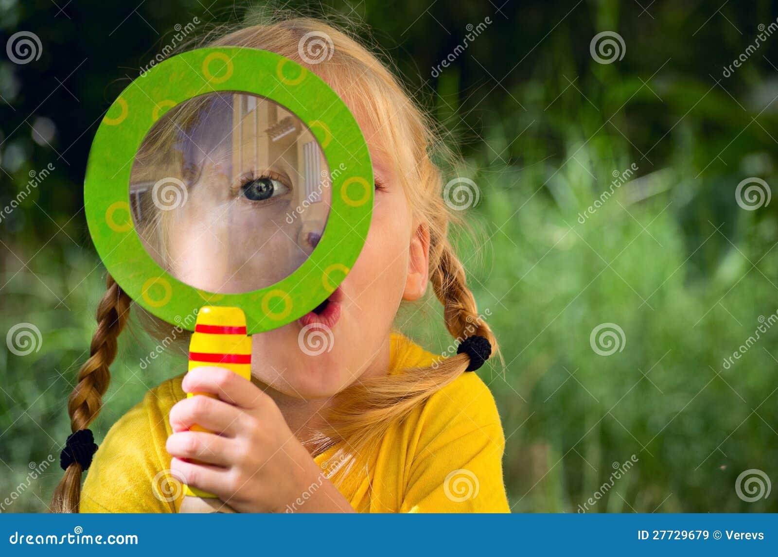 Mädchen, das durch ein Vergrößerungsglas schaut
