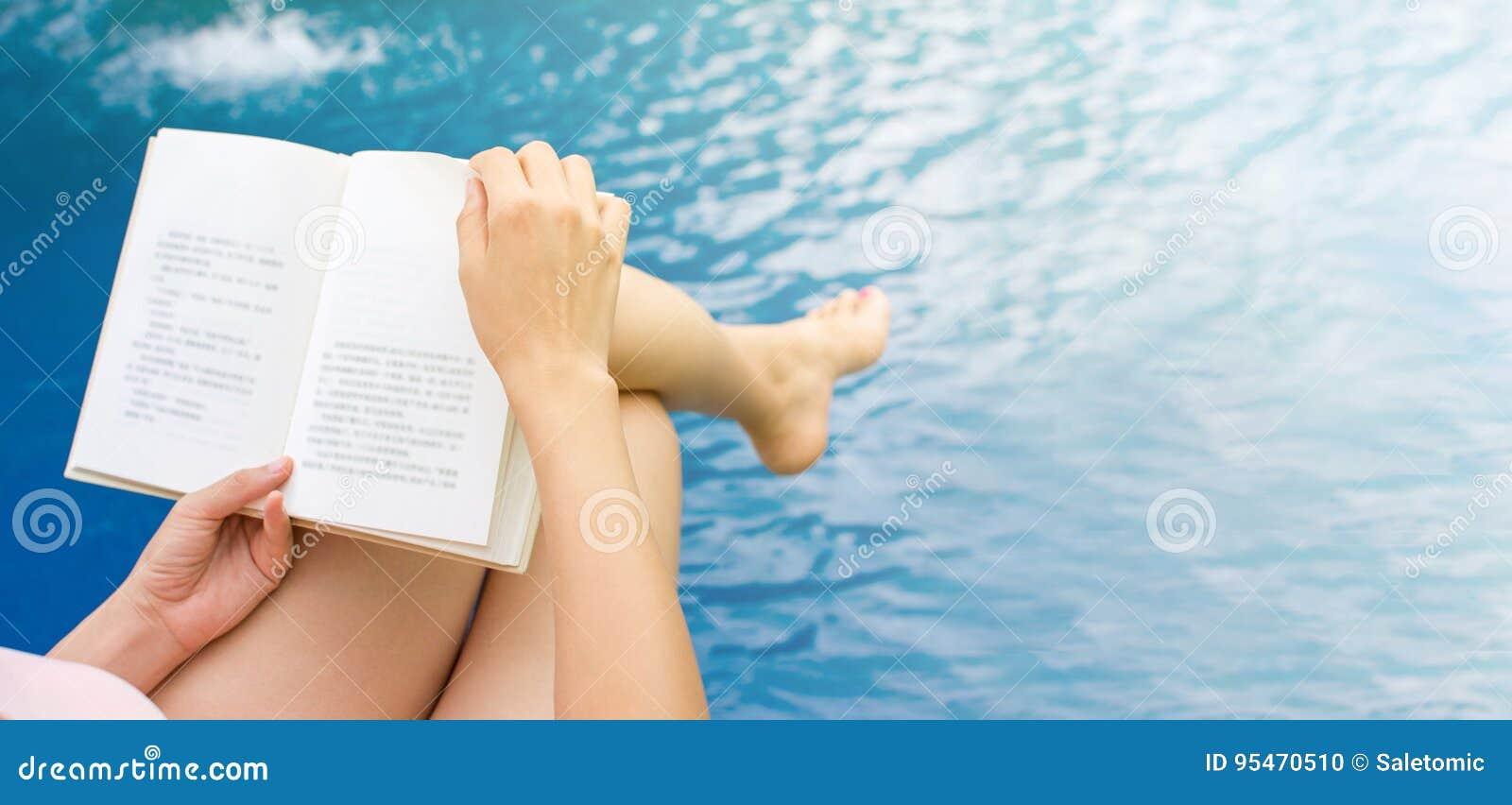 Mädchen, das ein Buch durch das Pool liest