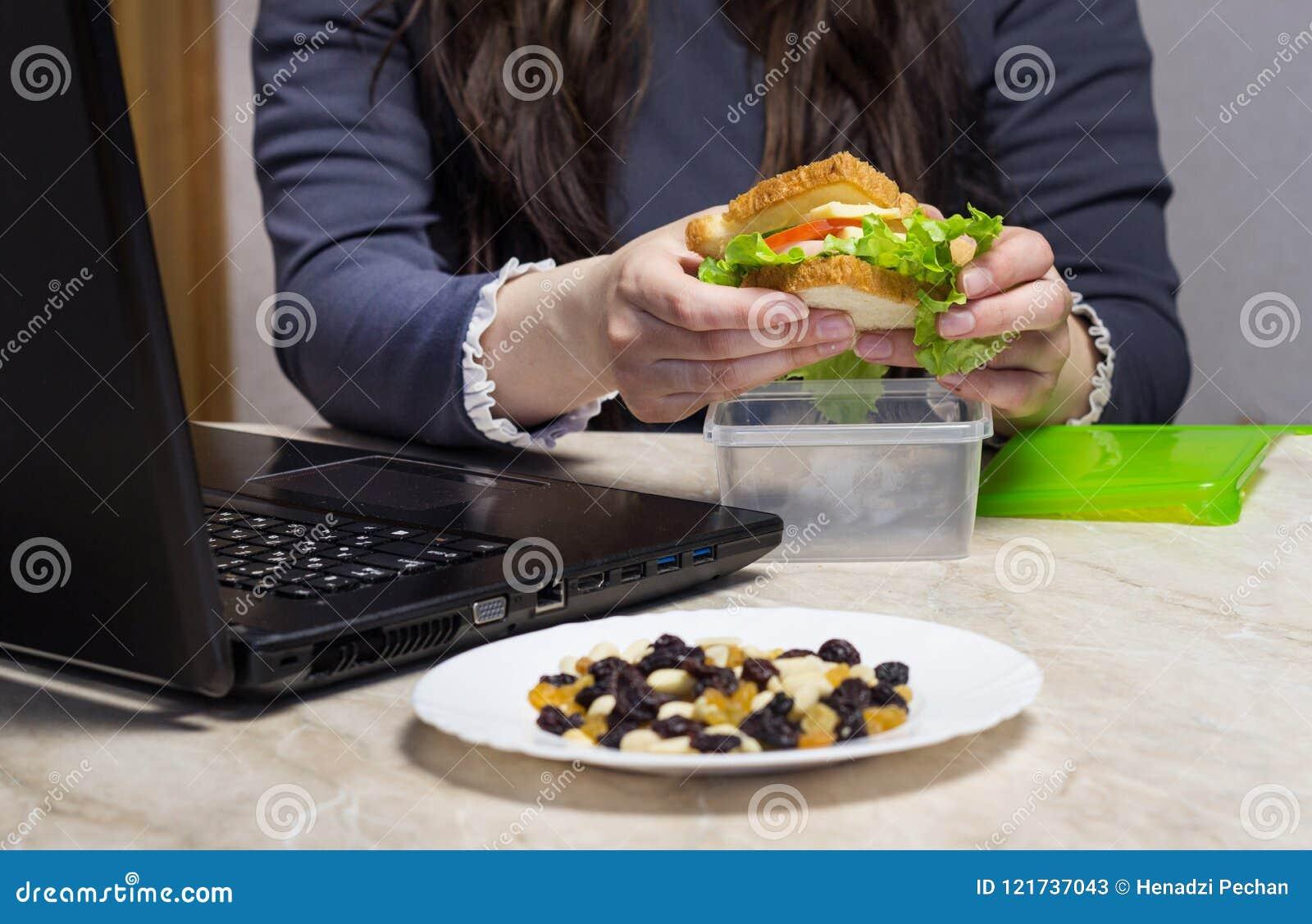 Mädchen, das ein Sandwich hält und oben an einem Laptop, Abschluss, Kalorien arbeitet